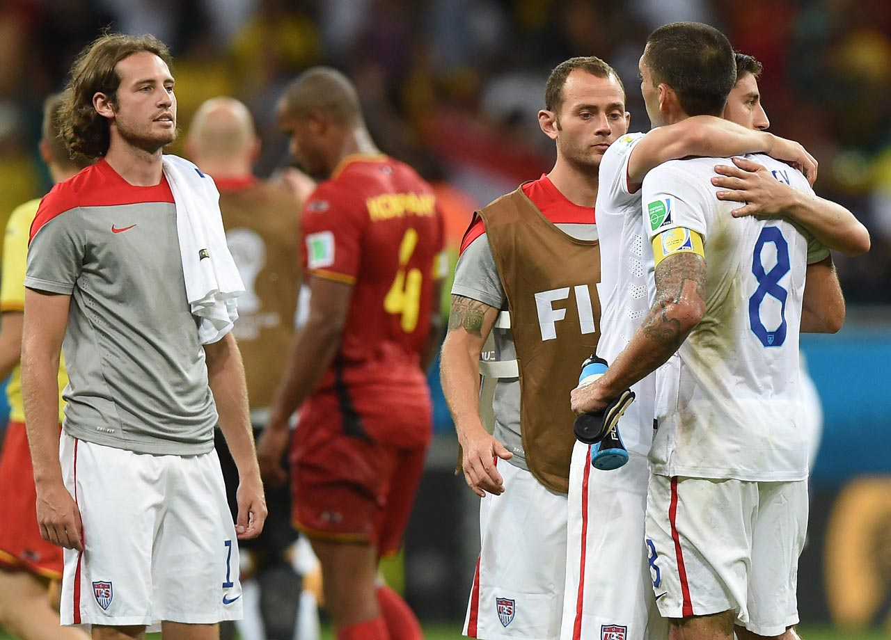American players console each other after the loss while Belgian players celebrate in the background.