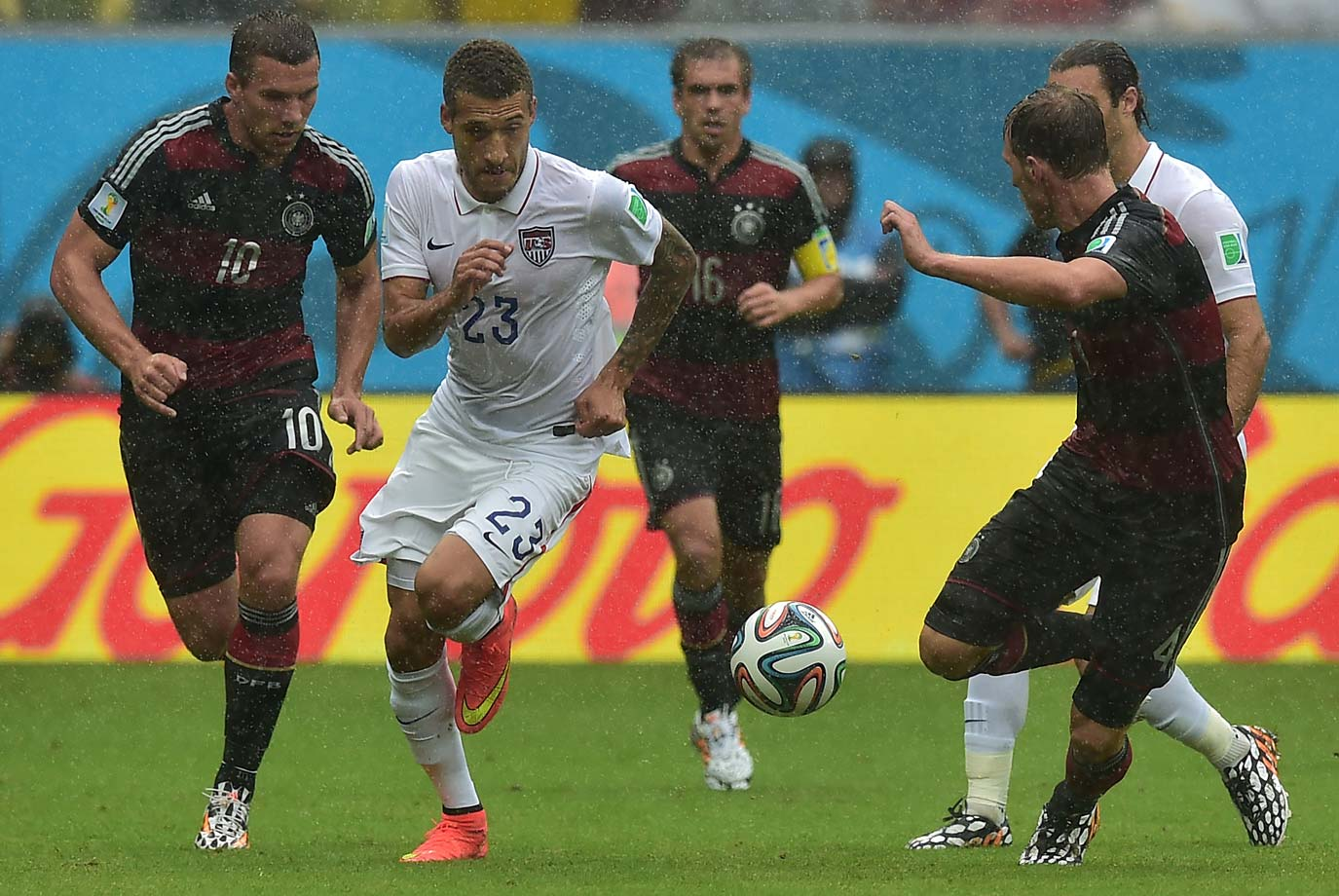 Germany's forward Lukas Podolski (left) and US defender Fabian Johnson vie for the ball.