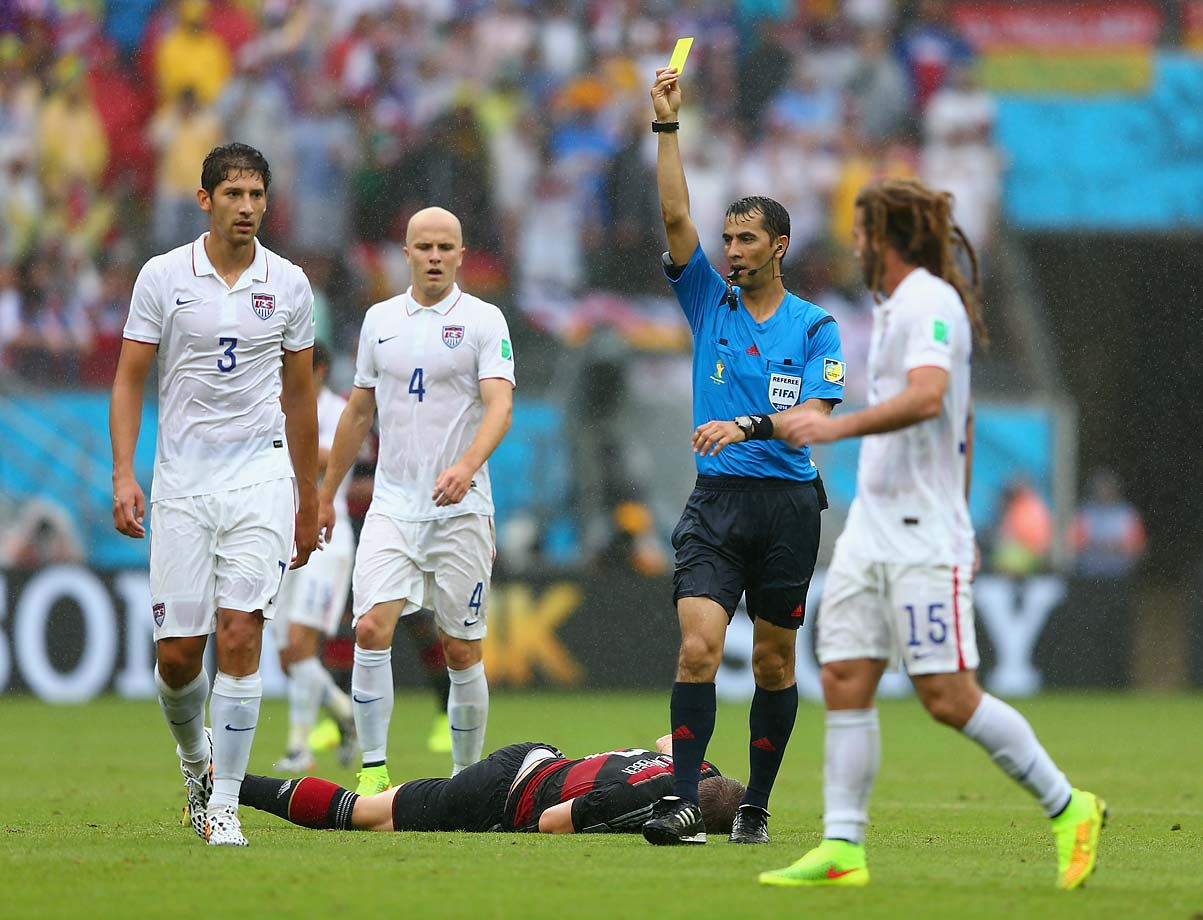 Omar Gonzalez of the United States is shown a yellow card by referee Ravshan Irmatov after a foul on Bastian Schweinsteiger of Germany.