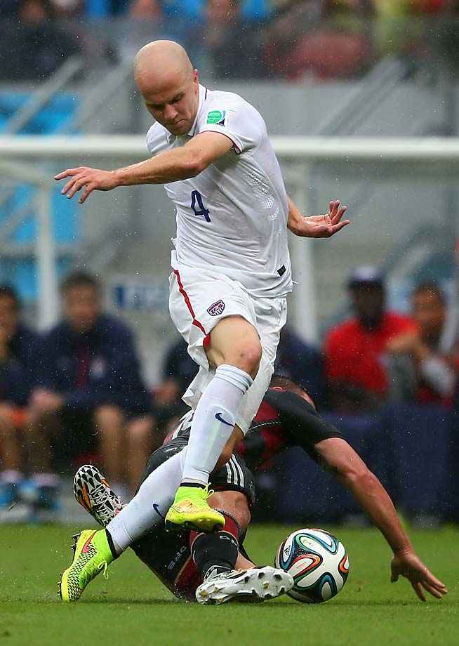 Michael Bradley is challenged by Lukas Podolski.