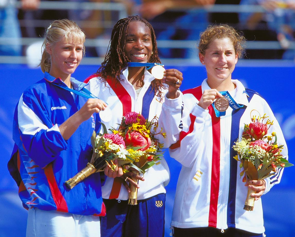 Williams holds up her gold medal at the Sydney Olympics with silver medalist Elena Dementieva, whom she beat 6-2, 6-4, and bronze medalist Monica Seles. Williams took home another gold medal as part of the winning doubles team with Serena.