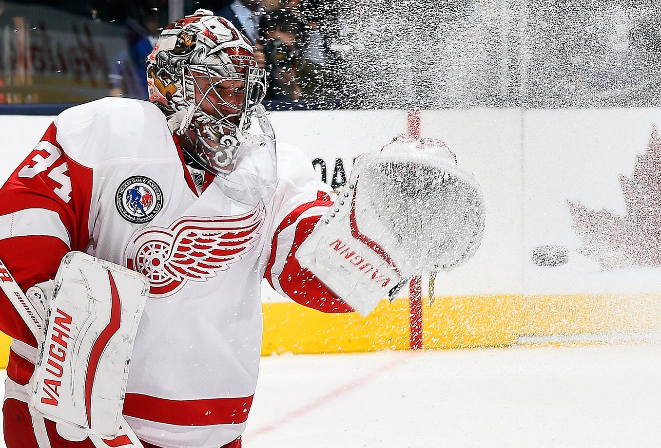 Petr Mrazek of the Detroit Red Wings makes a save through a spray of ice against the Toronto Maple Leafs.