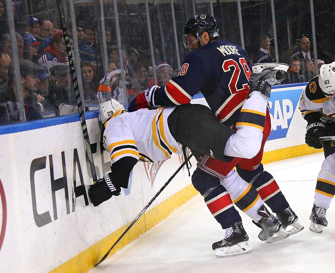 Dominic Moore of the New York Rangers pushes Landon Ferraro of the Boston Bruins into the boards at Madison Square Garden.