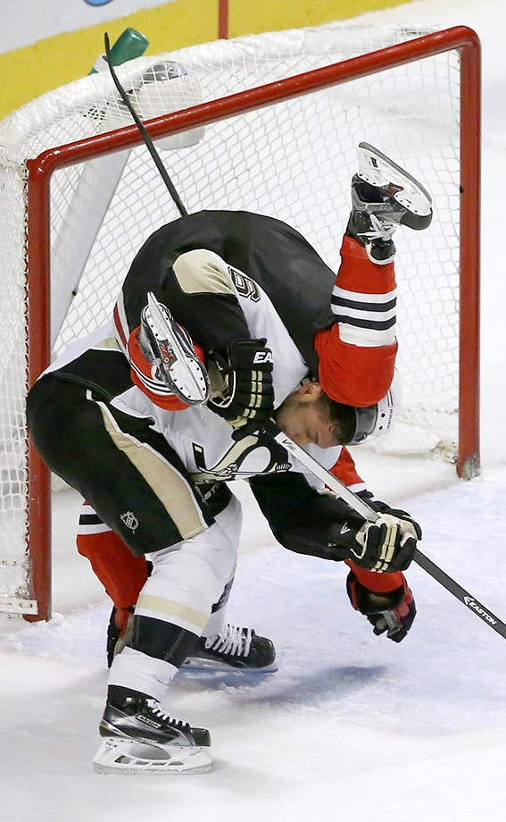Trevor Daley of the Pittsburgh Penguins upends Dennis Rasmussen of the Chicago Blackhawks.