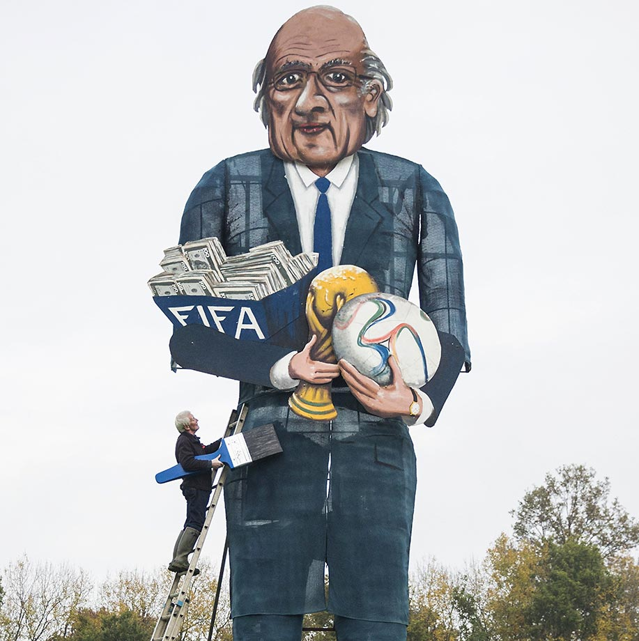 British artist Frank Shepherd of the Edenbridge Bonfire Society puts the finishing touches to a giant effigy of suspended FIFA president Sepp Blatter.