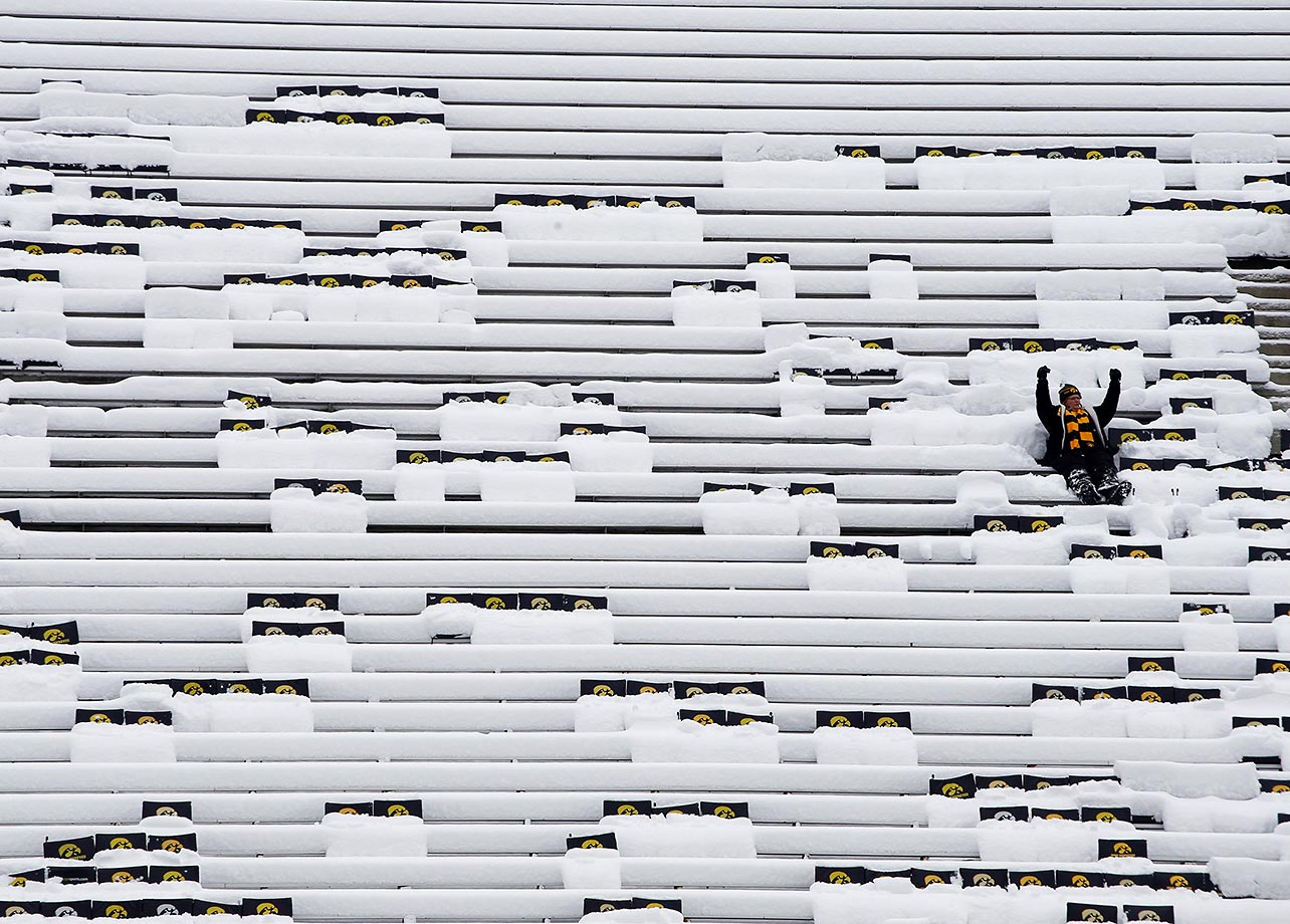A fan sits in a snow-filled Kinnick Stadium before the Iowa Hawkeyes played the Purdue Boilermakers.