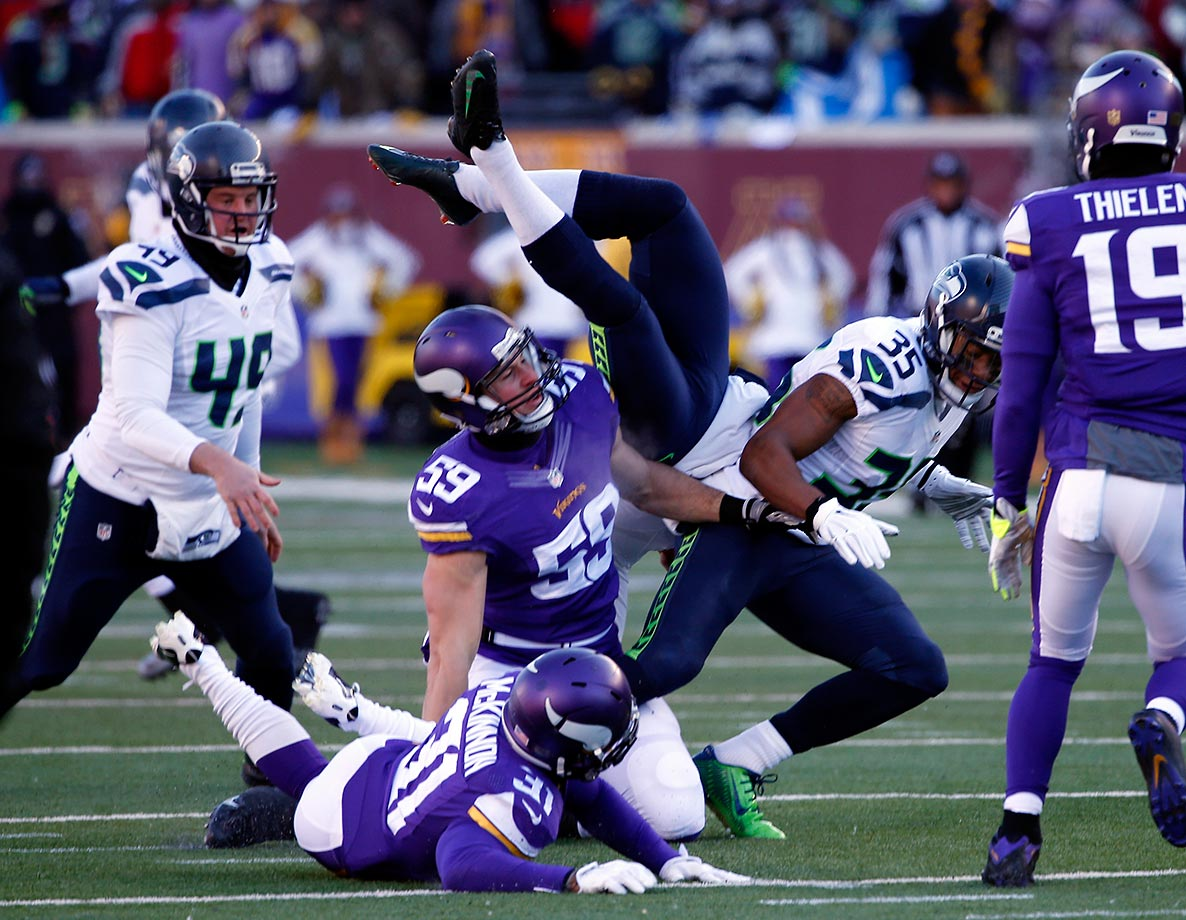 Punter Jon Ryan of the Seattle Seahawks flips over as he runs the ball against the Minnesota Vikings.