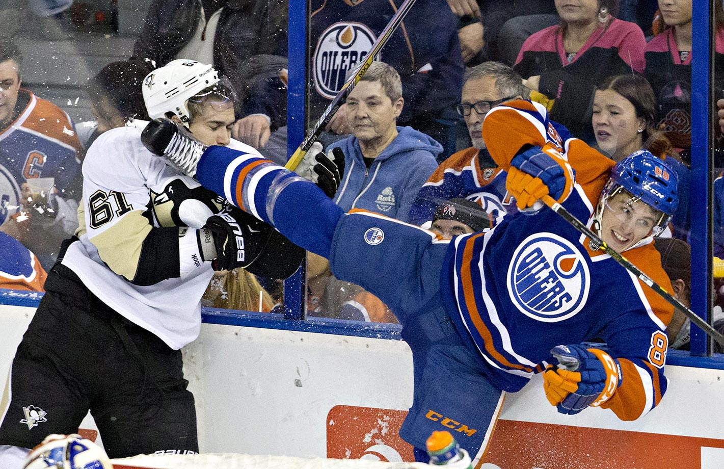 Sergei Plotnikov of the Pittsburgh Penguins gets a skate from Brandon Davidson of the Edmonton Oilers.