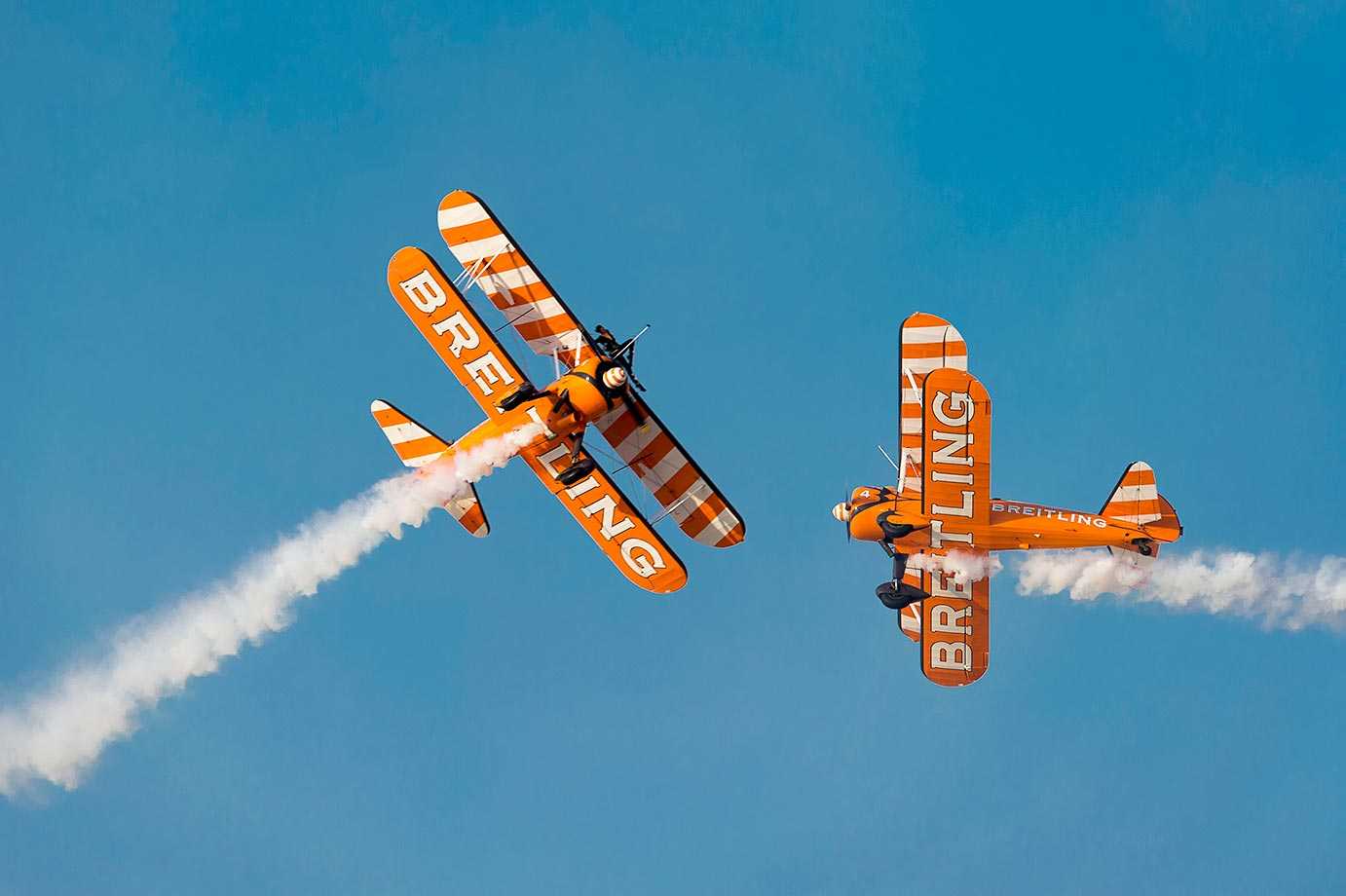The Breitling Wingwalkers team performs aerial aerobatic formations with Boeing Stearman biplanes during the Dubai Airshow.