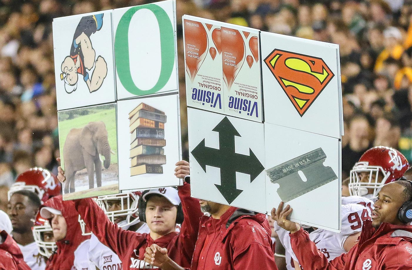 The Oklahoma Sooners send in signals using sign boards at a game against Baylor.