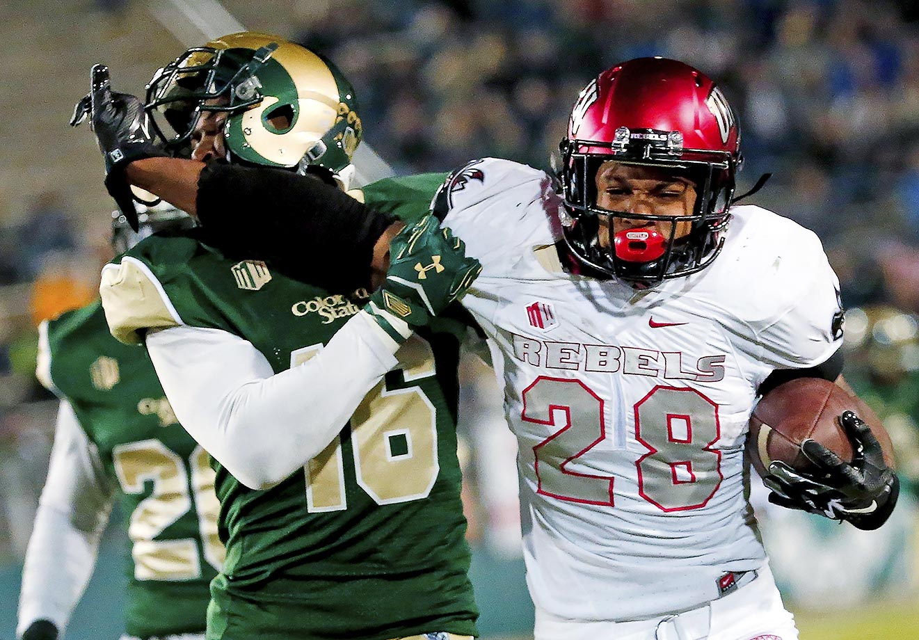 Keith Whitely of UNLV stiff-arms Trent Matthews of Colorado State, drawing a facemask penalty.