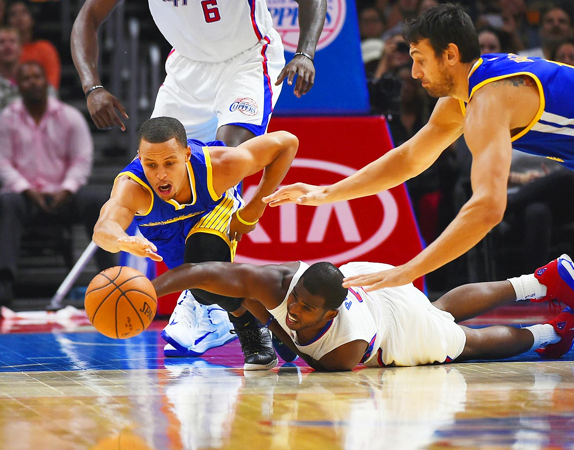 Stephen Curry of the Golden State Warriors and Chris Paul of the Los Angeles Clippers reach for a ball during their first preseason game. The Warriors won 112-94.