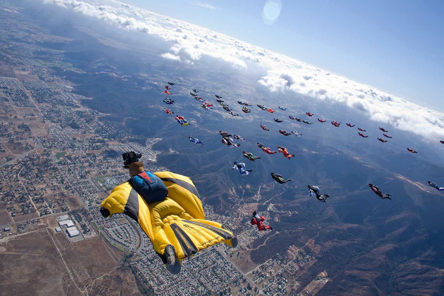 Wingsuit skydivers fly through the air above Lake Elsinore, California traveling at speeds over 100 mph.