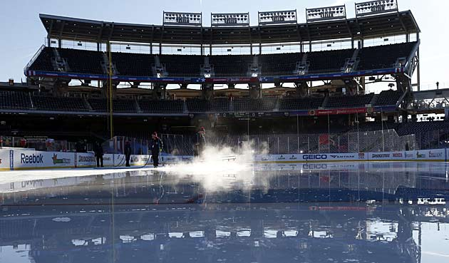 The crew sprays down the rink before pregame practice.