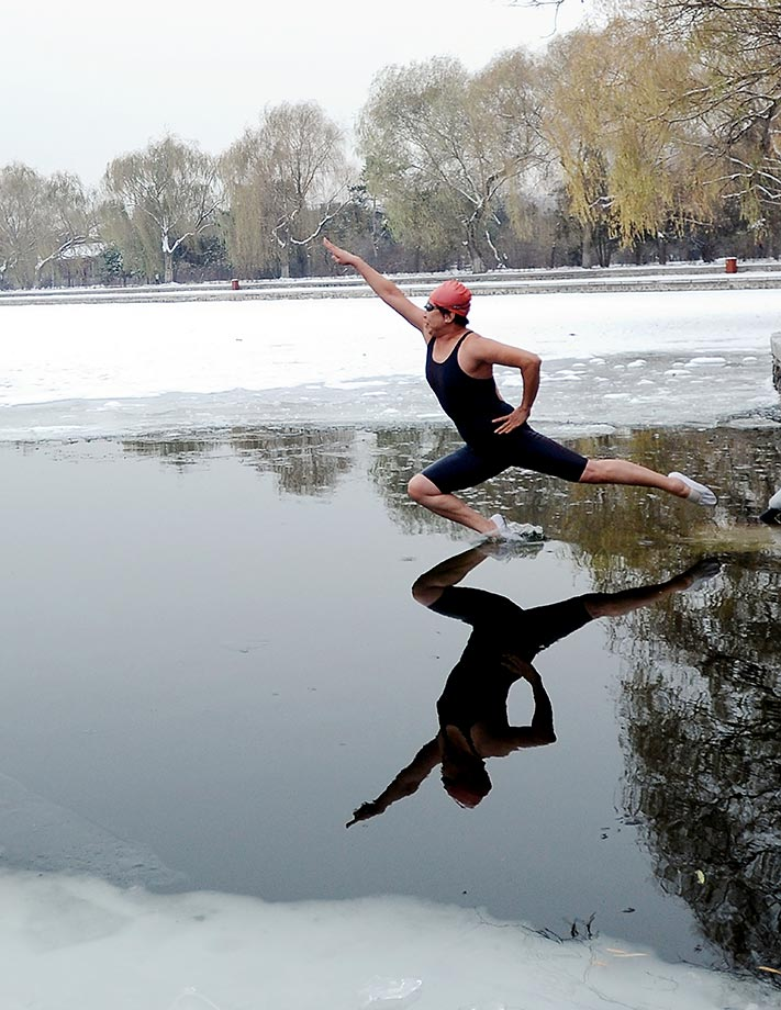 A winter swimmer jumps into a partially frozen lake in Beiling Park in Shenyang, Liaoning Province of China.