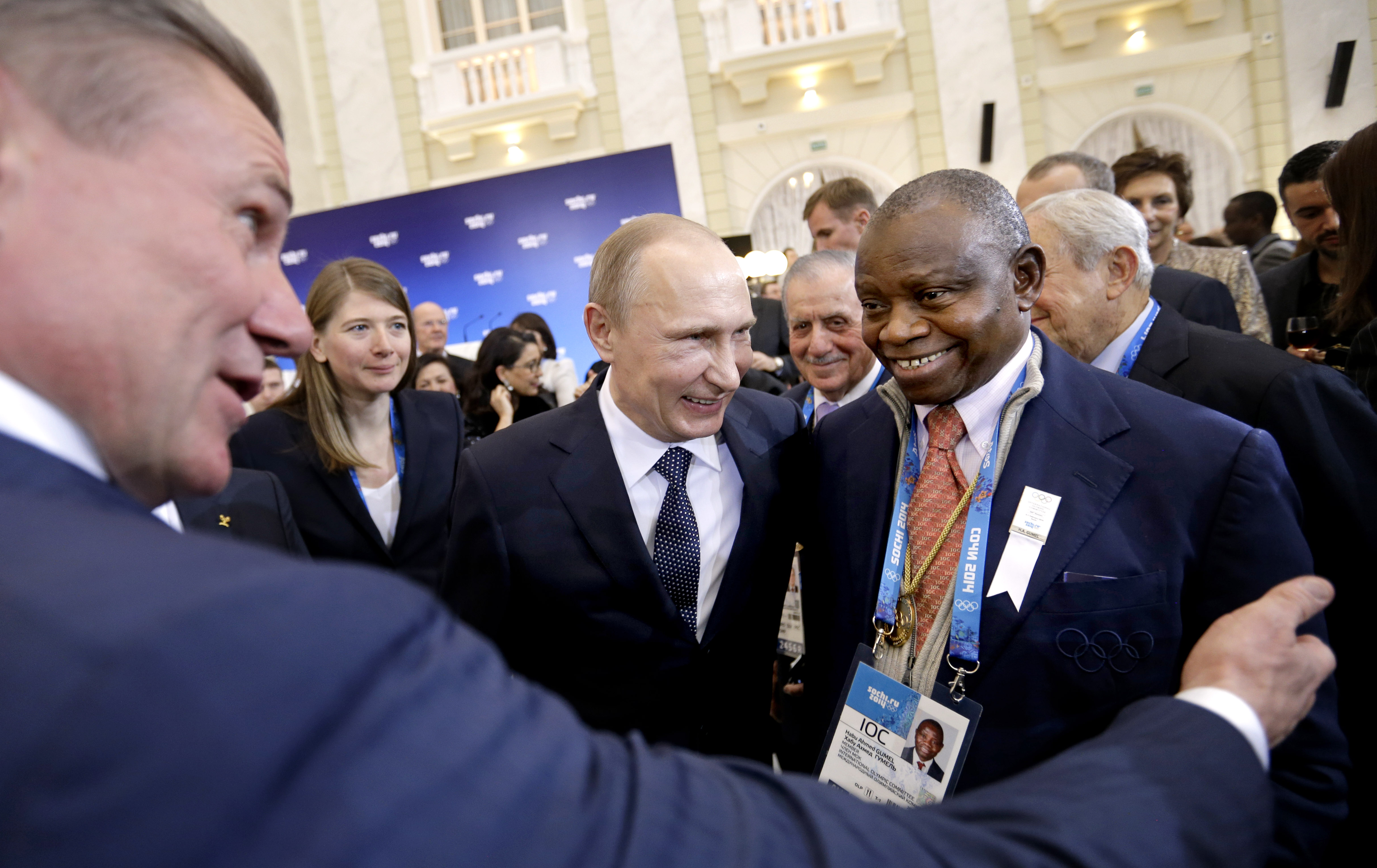Russian President Vladimir Putin, center, greets International Olympic Committee members Habu Ahmed Gumel, right, and  executive board member Sergei Bubka, left, at a welcoming event ahead of the upcoming 2014 Winter Olympics at the Rus Hotel, Tuesday, Feb. 4, 2014, in Sochi, Russia. (AP Photo/David Goldman, Pool)