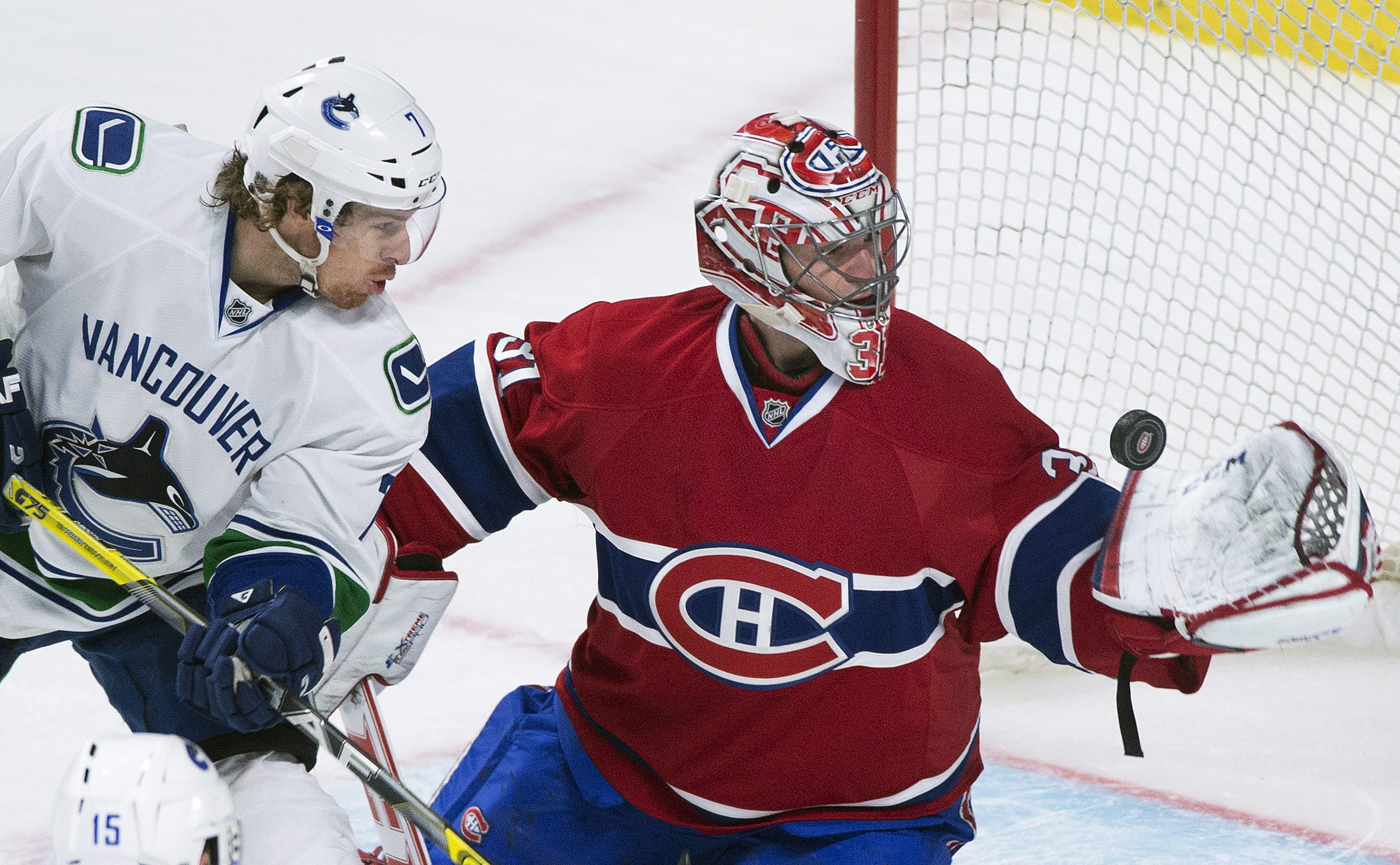 Montreal Canadiens goaltender Carey Price makes a save against Vancouver Canucks' David Booth during the third period of an NHL hockey game Thursday, Feb. 6, 2014, in Montreal. (AP Photo/The Canadian Press, Graham Hughes)