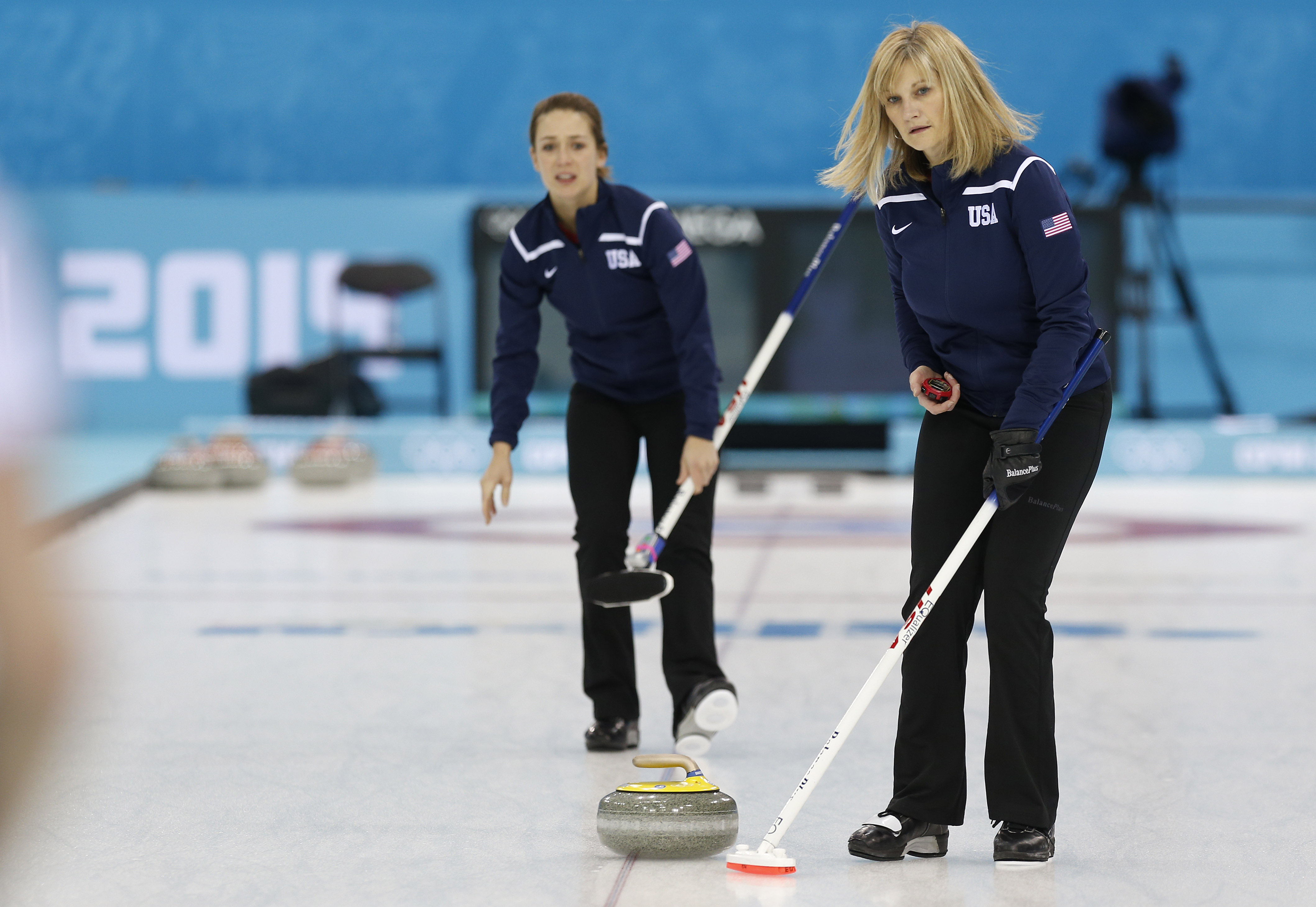 Team USA skip Erika Brown, right, uses a stopwatch to time the throw from teammate Jessica Schultz during the first day of curling training at the 2014 Winter Olympics, Saturday, Feb. 8, 2014, in Sochi, Russia. (AP Photo/Robert F. Bukaty)