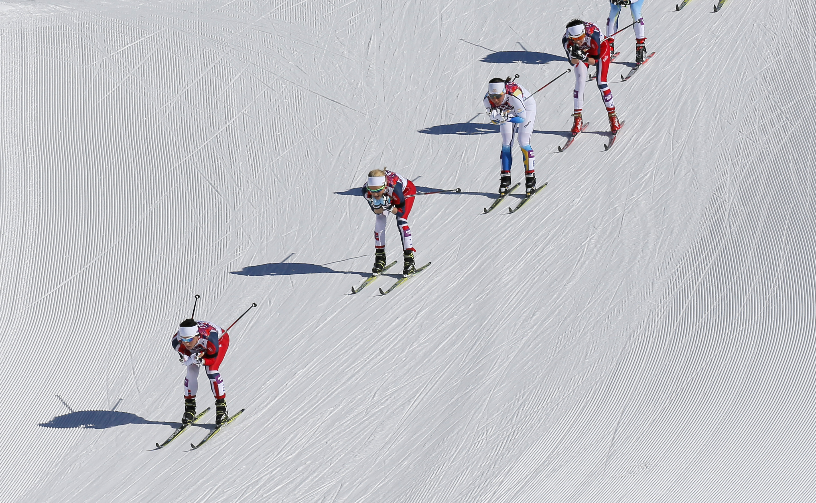 Norway's Marit Bjoergen, Norway's Therese Johaug, Sweden's Charlotte Kalla and Norway's Heidi Weng, from left, ski down a hill during the women's 15k skiathlon at the 2014 Winter Olympics, Saturday, Feb. 8, 2014, in Krasnaya Polyana, Russia. (AP Photo/Dmitry Lovetsky)