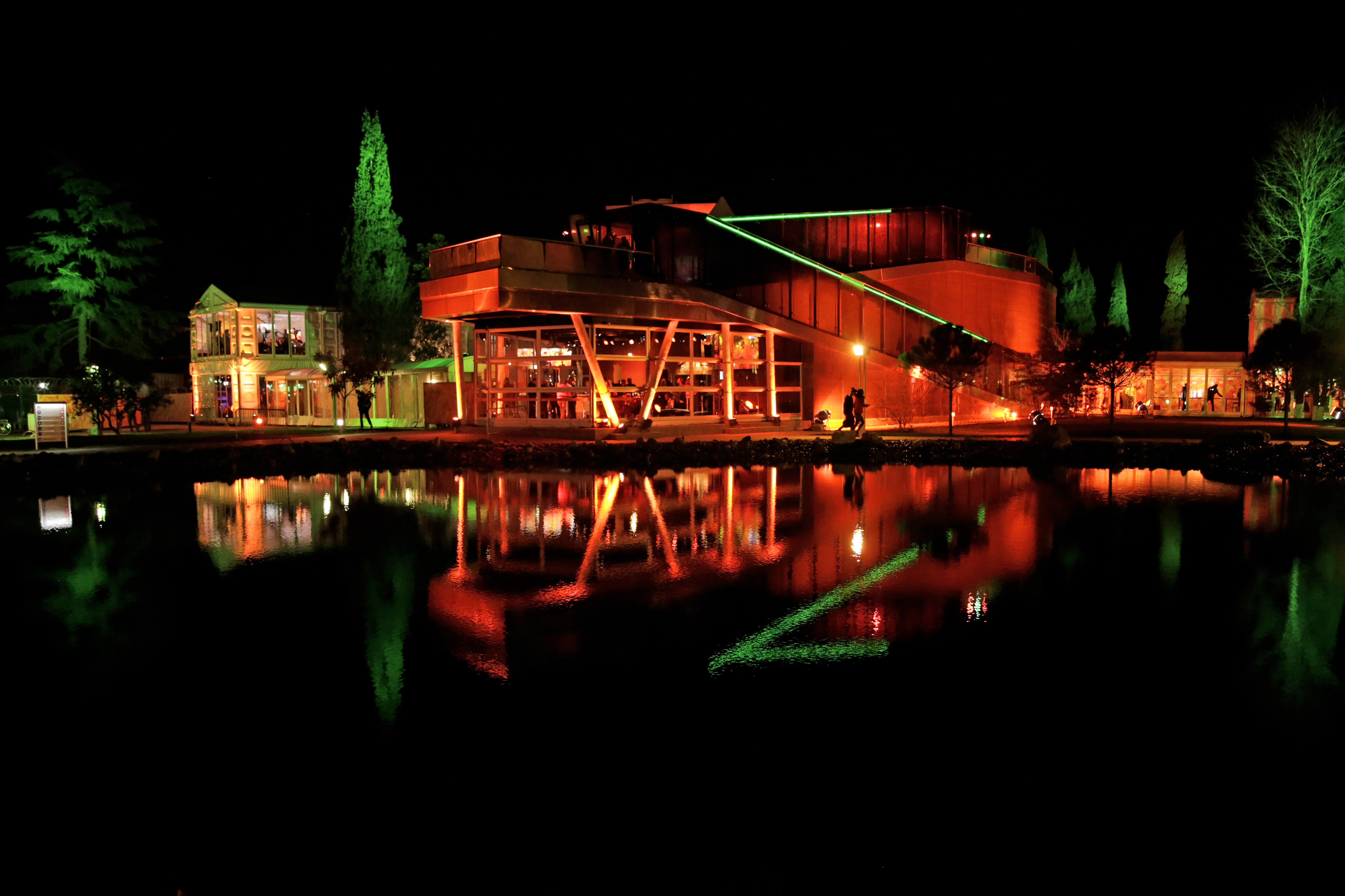 The orange-lit Holland House is reflected in a pond following the appearance of gold medallist Sven Kramer of the Netherlands on stage in front of fans after he set a new Olympic record to  win the 5000 meters speedskating race at the 2014 Winter Olympics in Sochi, Russia, Saturday, Feb. 8, 2014. (AP Photo/Matt Dunham)
