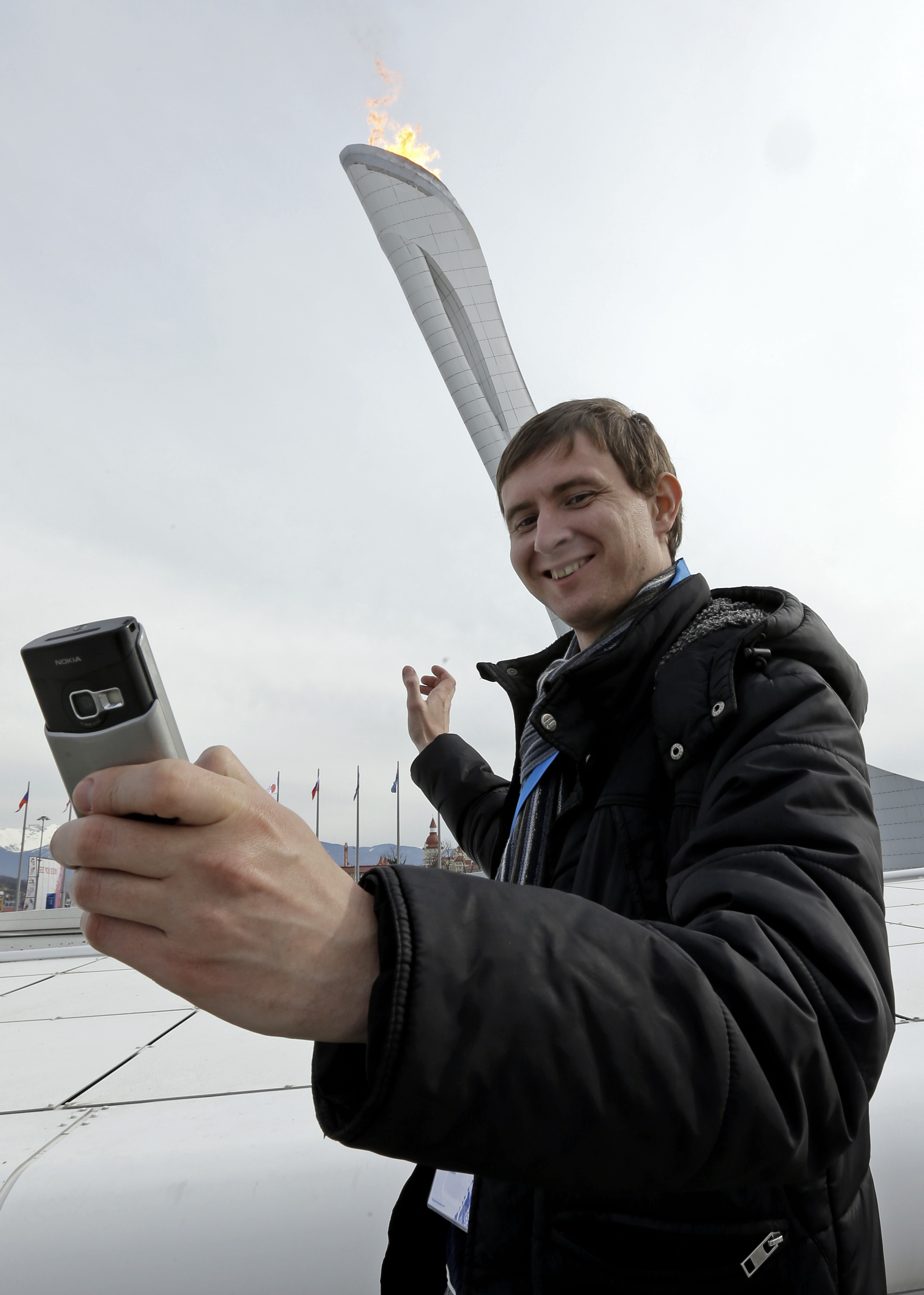 Sartakov Pavel Albertovich takes a selfie in front of the Olympic Cauldron at the 2014 Winter Olympics, Sunday, Feb. 9, 2014, in Sochi, Russia. (AP Photo/Morry Gash)