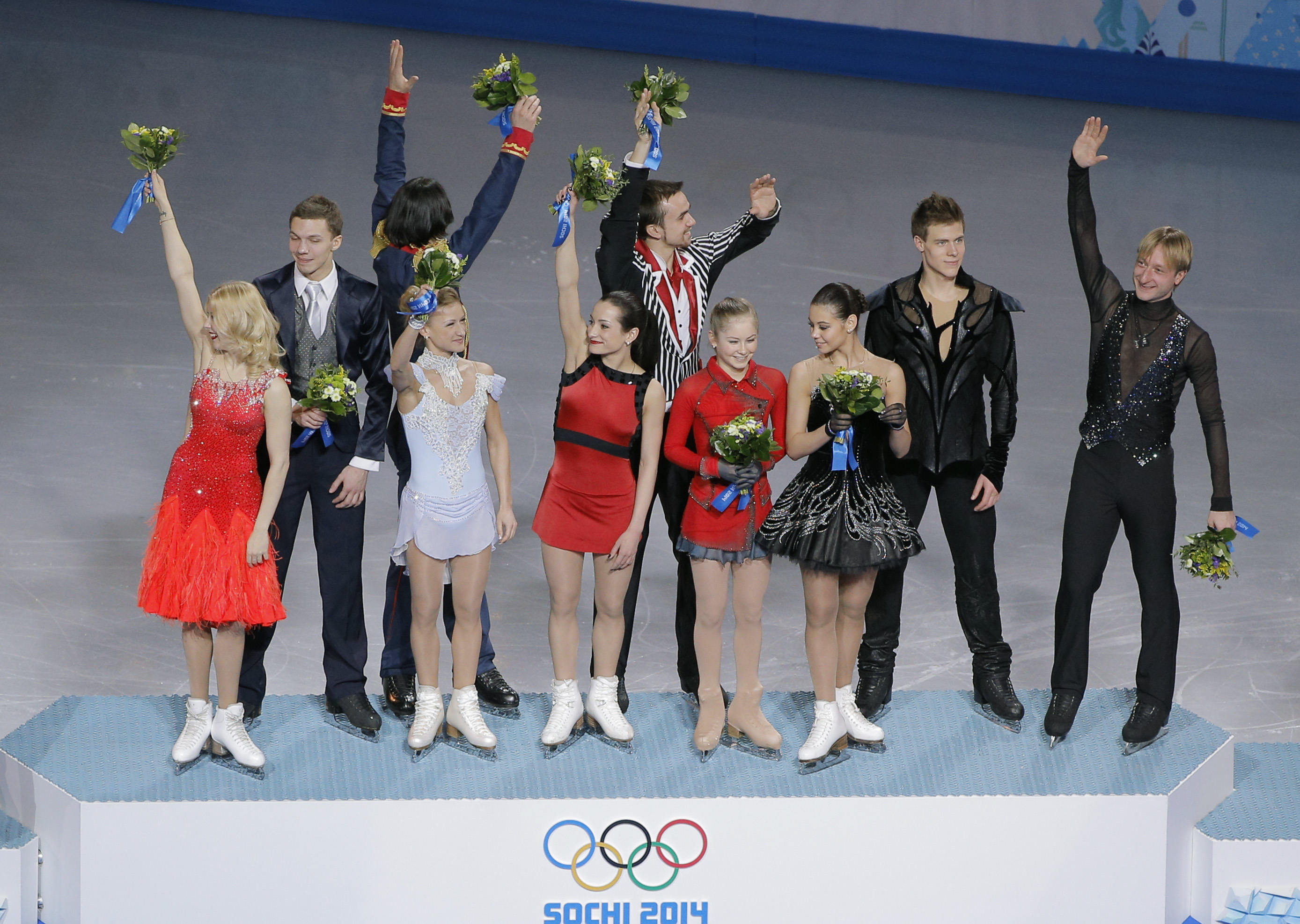 The Russian team wave to spectators from the podium during the flower ceremony after placing first in the team figure skating competition at the Iceberg Skating Palace during the 2014 Winter Olympics, Sunday, Feb. 9, 2014, in Sochi, Russia. (AP Photo/Vadim Ghirda)