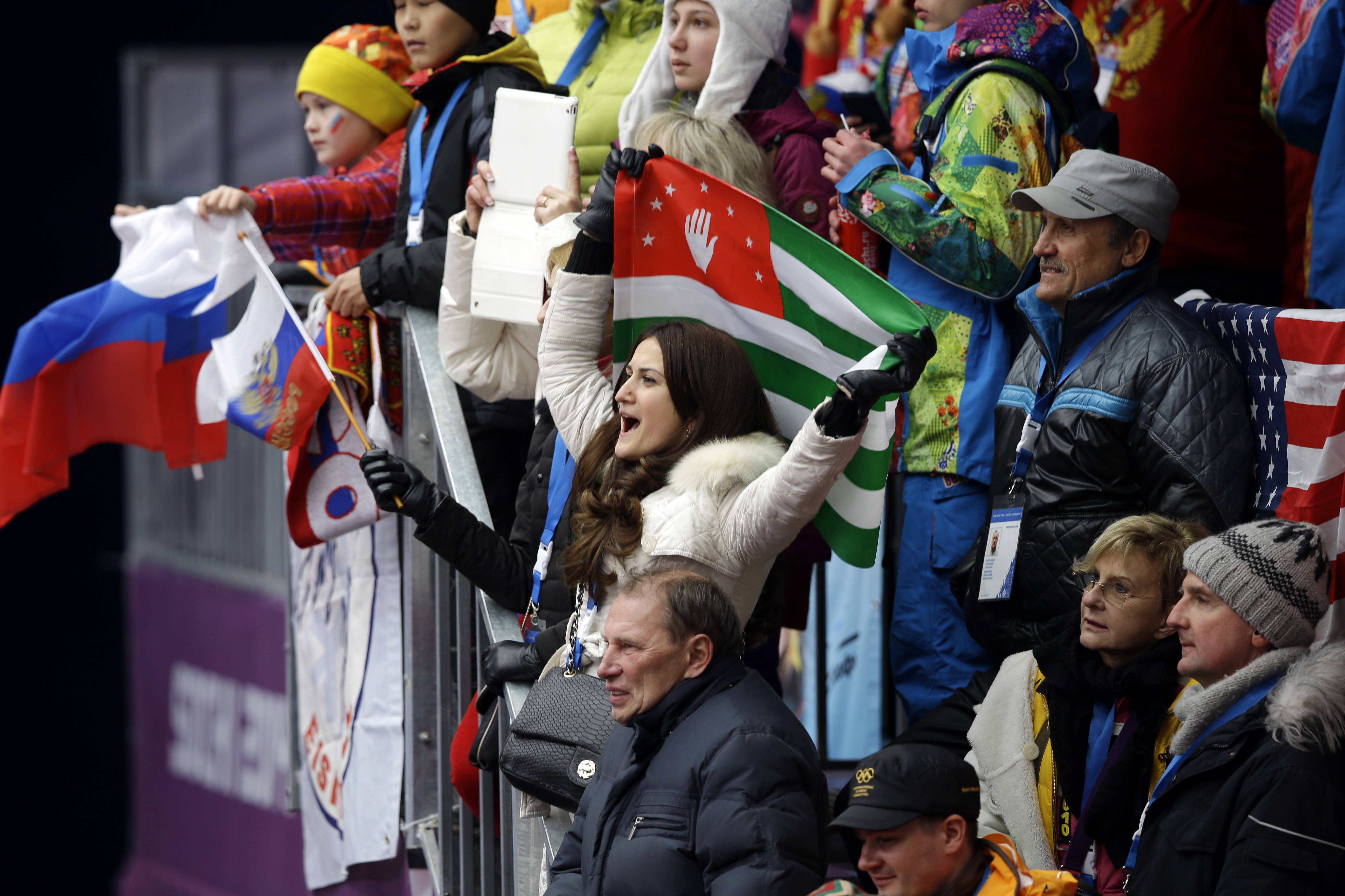Fans cheer during the women's singles luge competition at the 2014 Winter Olympics, Monday, Feb. 10, 2014, in Krasnaya Polyana, Russia. (AP Photo/Dita Alangkara)