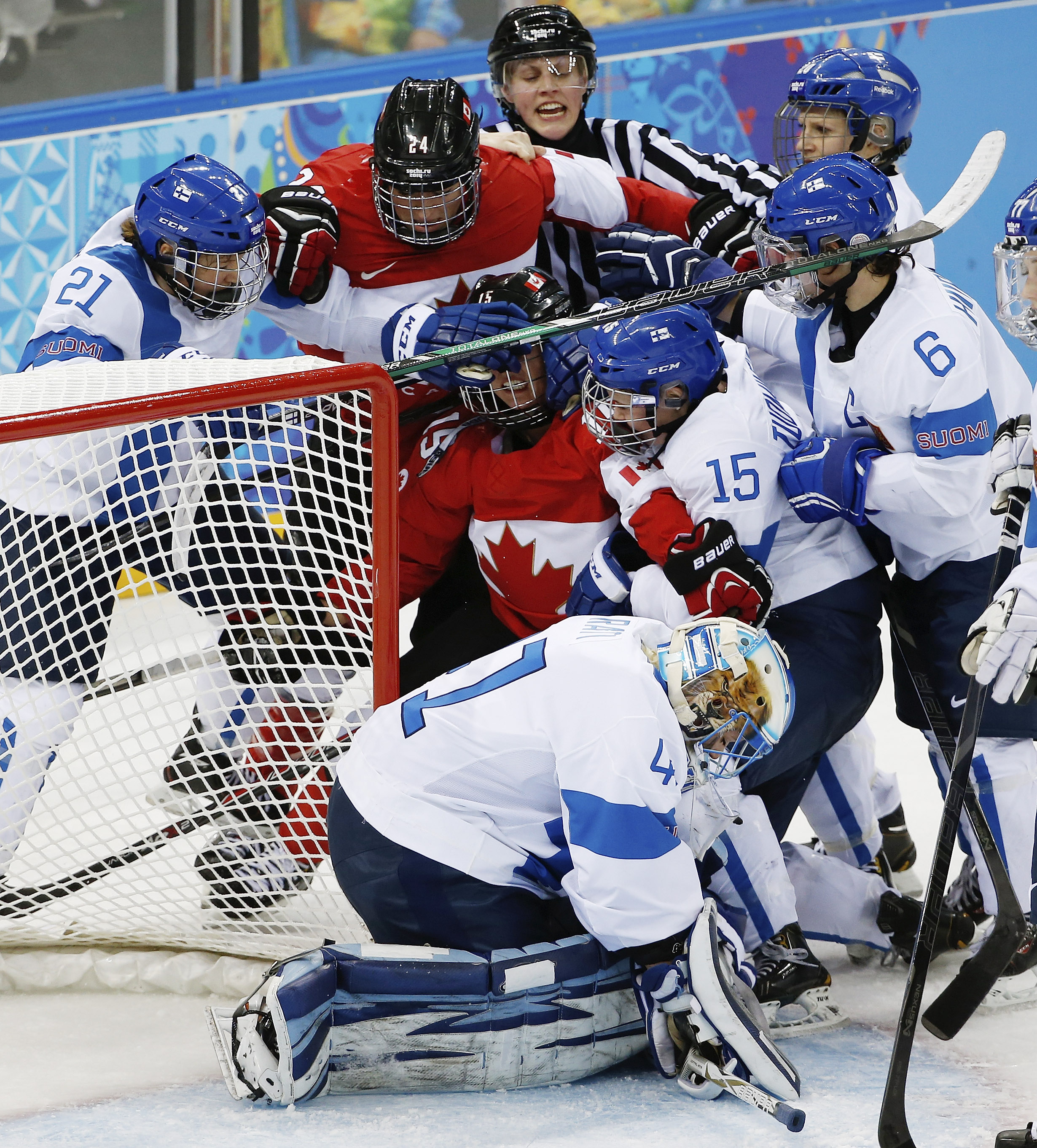 The referee breaks up a scuffle between Team Canada and Team Finland that resulted in two penalties against Canada during the second period of the 2014 Winter Olympics women's ice hockey game at Shayba Arena, Monday, Feb. 10, 2014, in Sochi, Russia. (AP Photo/Petr David Josek)