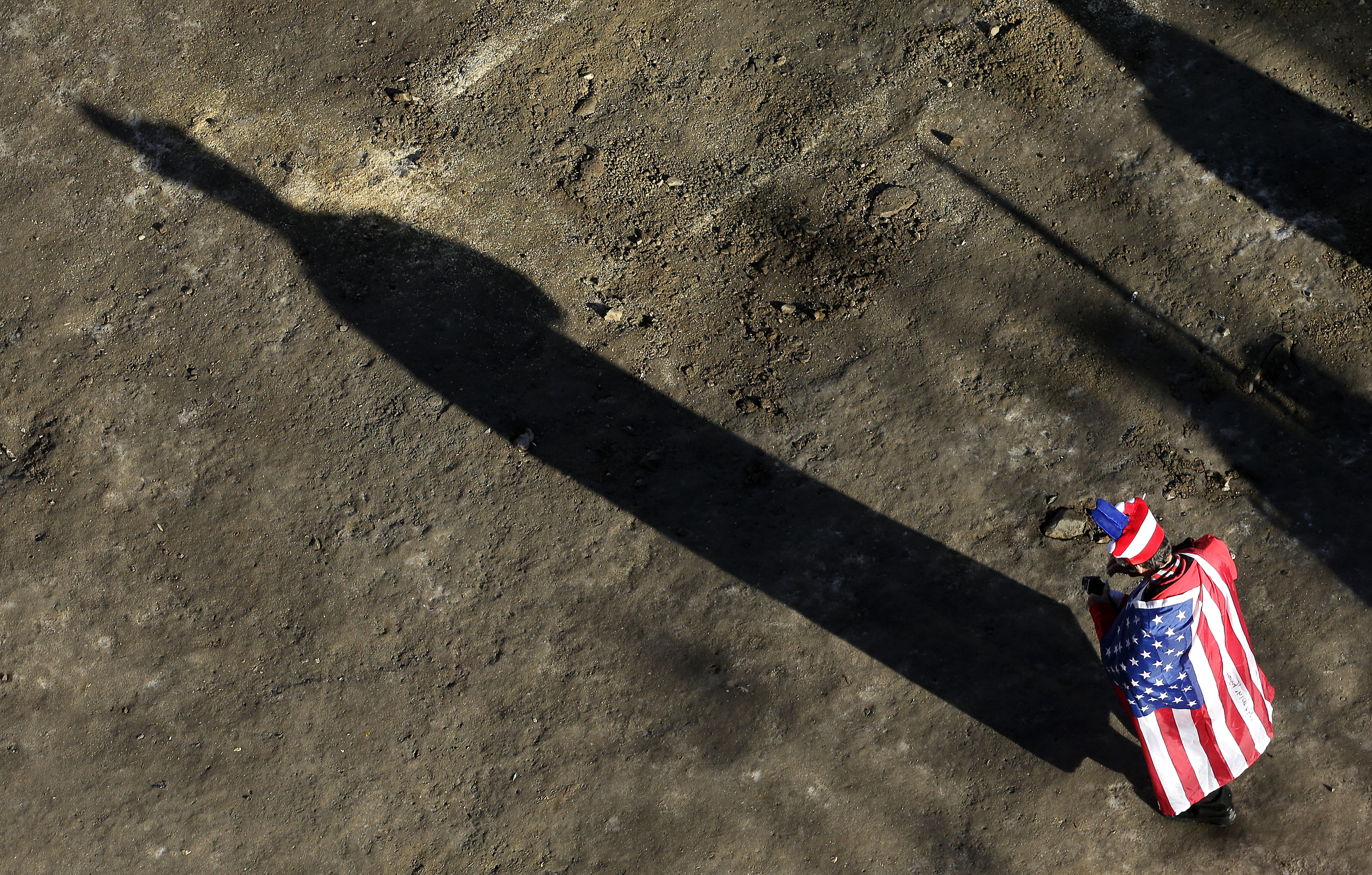 A fan wearing an United States flag arrives at the women's downhill competition at the 2014 Winter Olympics, Wednesday, Feb. 12, 2014, in Krasnaya Polyana, Russia. (AP Photo/Charlie Riedel)