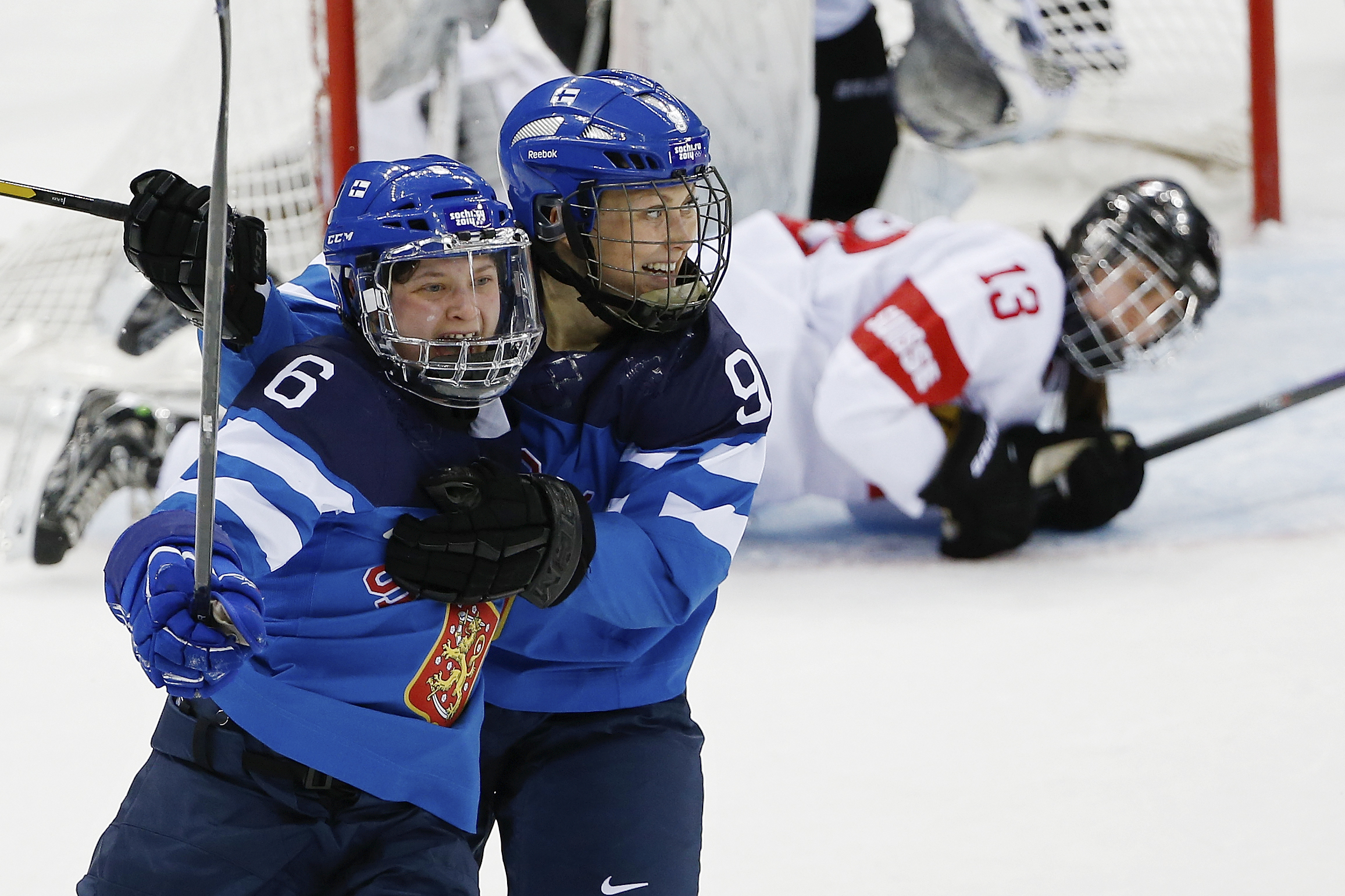 Jenni Hiirikoski of Finland, left, celebrates her game winning goal in overtime with teammate Venla Hovi, right, as Sara Benz of Switzerland looks on in the background during the 2014 Winter Olympics women's ice hockey game at Shayba Arena, Wednesday, Feb. 12, 2014, in Sochi, Russia. Finland defeated Switzerland 4-3 in overtime. (AP Photo/Petr David Josek)