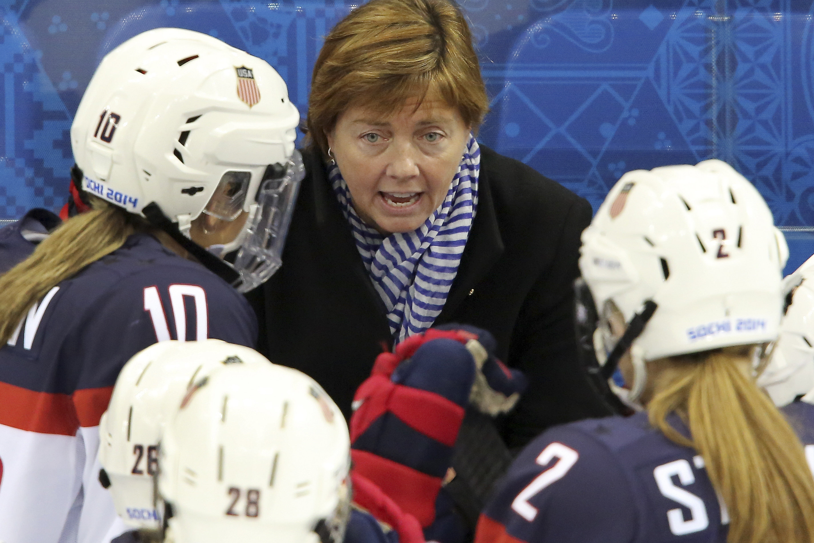 USA head coach Katey Stone talks to the team during a break in the action at the 2014 Winter Olympics women's ice hockey game between Canada and the United States at Shayba Arena, Wednesday, Feb. 12, 2014, in Sochi, Russia. (AP Photo/J. David Ake)