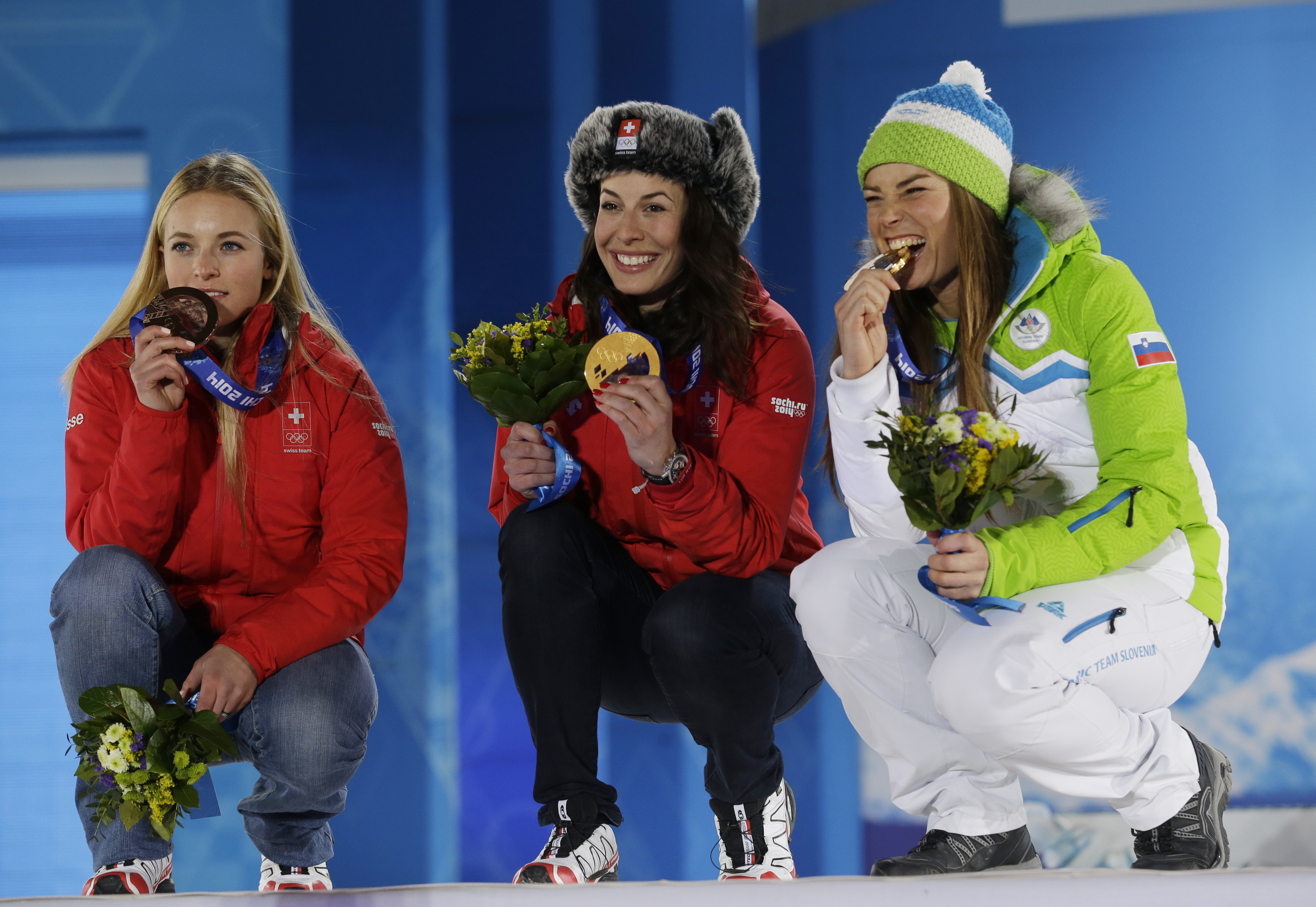 Women's downhill medalists, from left, Switzerland's Lara Gut, bronze, Switzerland's Dominique Gisin and Slovenia's Tina Maze who tied for the gold, pose with their medals at the 2014 Winter Olympics in Sochi, Russia, Wednesday, Feb. 12, 2014.  (AP Photo/Morry Gash)