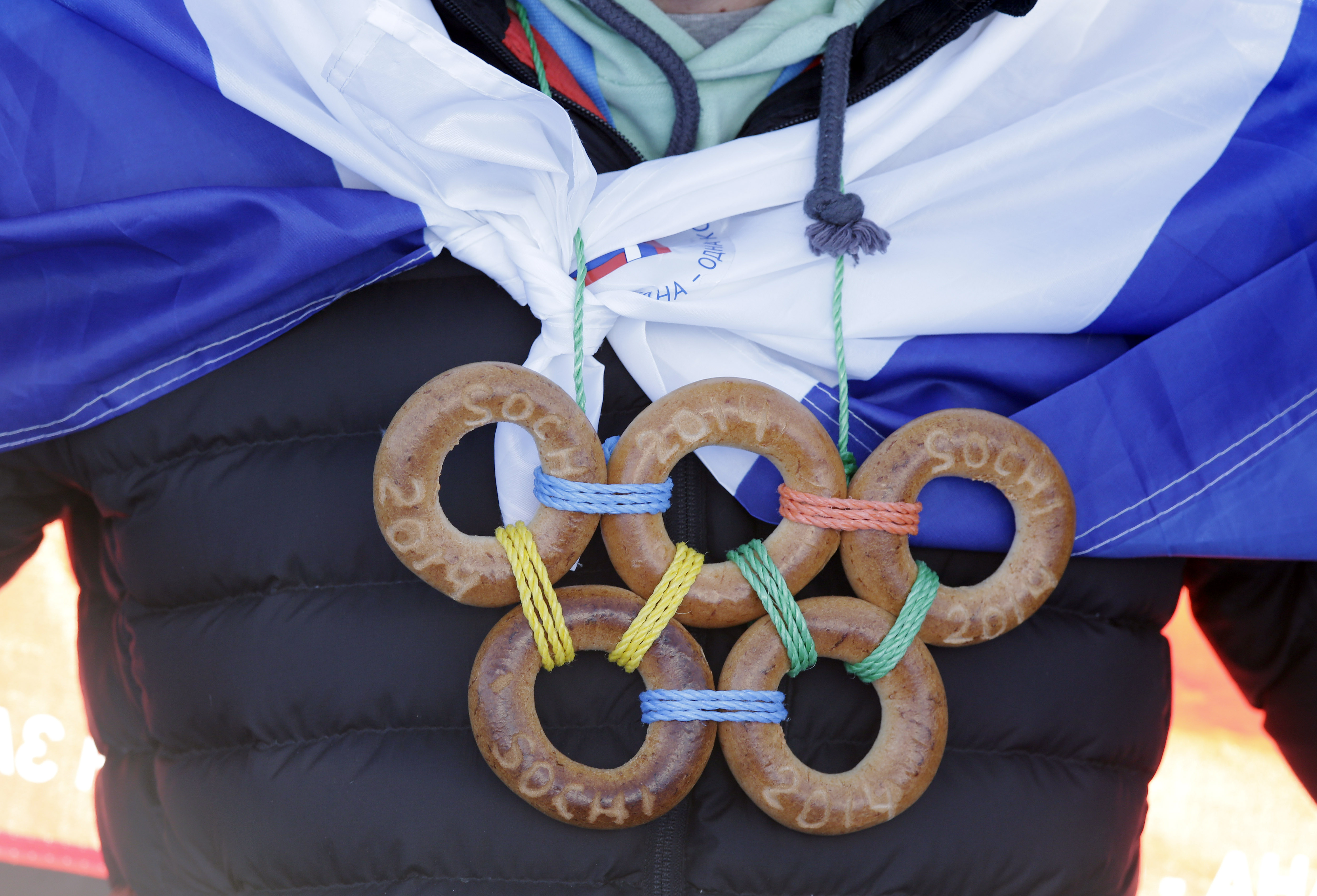 A spectator wears the Olympic rings made from bagels during the men's ski slopestyle qualifying at the Rosa Khutor Extreme Park, at the 2014 Winter Olympics, Thursday, Feb. 13, 2014, in Krasnaya Polyana, Russia. (AP Photo/Andy Wong)