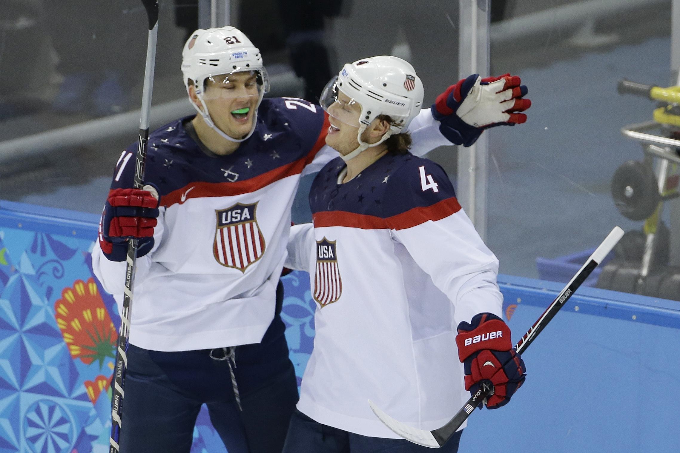 USA defenseman John Carlson, right, is congratulated for his goal against Slovakia by USA forward James van Riemsdyk during the 2014 Winter Olympics men's ice hockey game at Shayba Arena, Thursday, Feb. 13, 2014, in Sochi, Russia. (AP Photo/Matt Slocum)