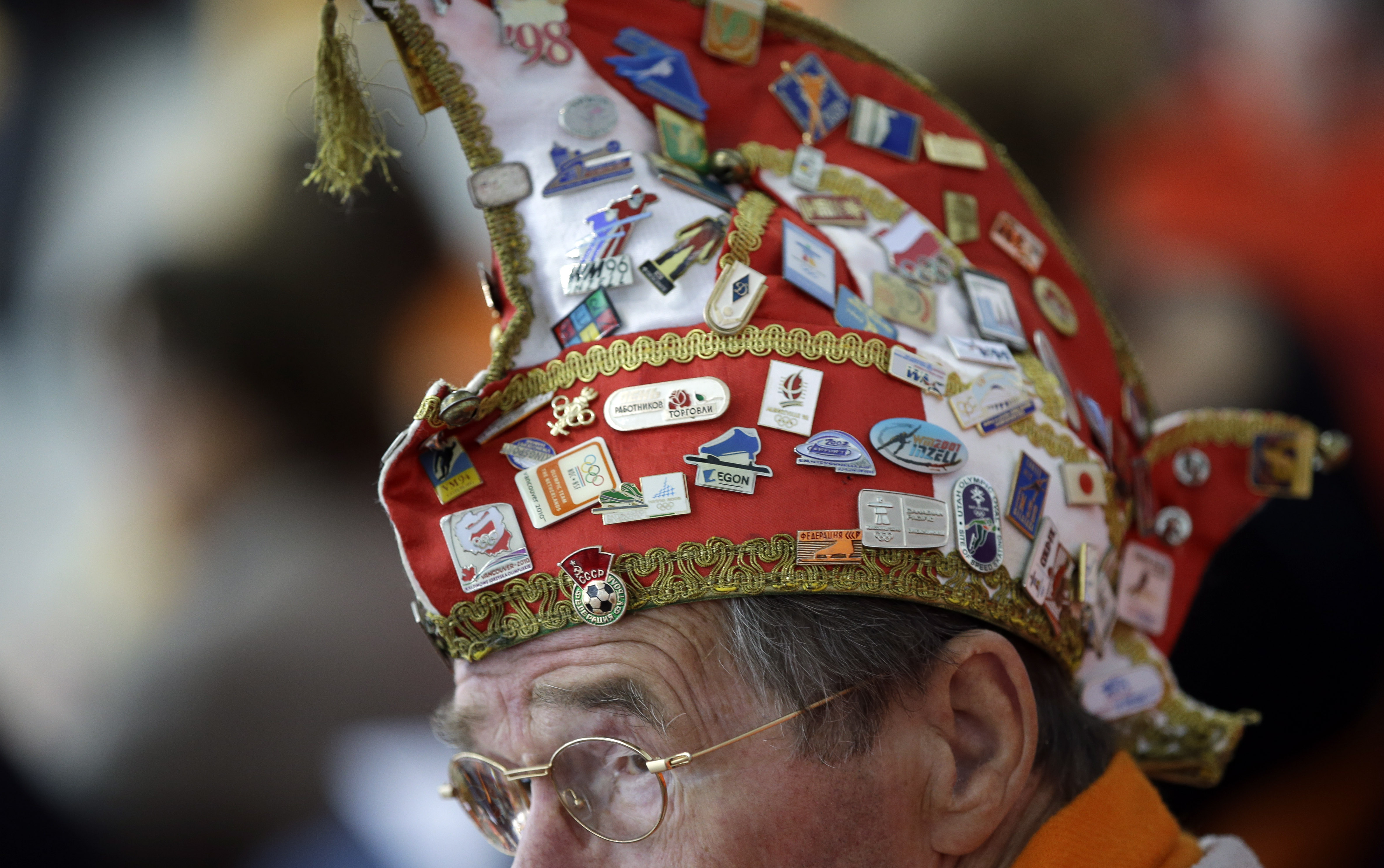 A Dutch skating fan, his hat filled with Olympic pins, watches the women's 1,000-meter speedskating race at the Adler Arena Skating Center during the 2014 Winter Olympics in Sochi, Russia, Thursday, Feb. 13, 2014. (AP Photo/David J. Phillip )