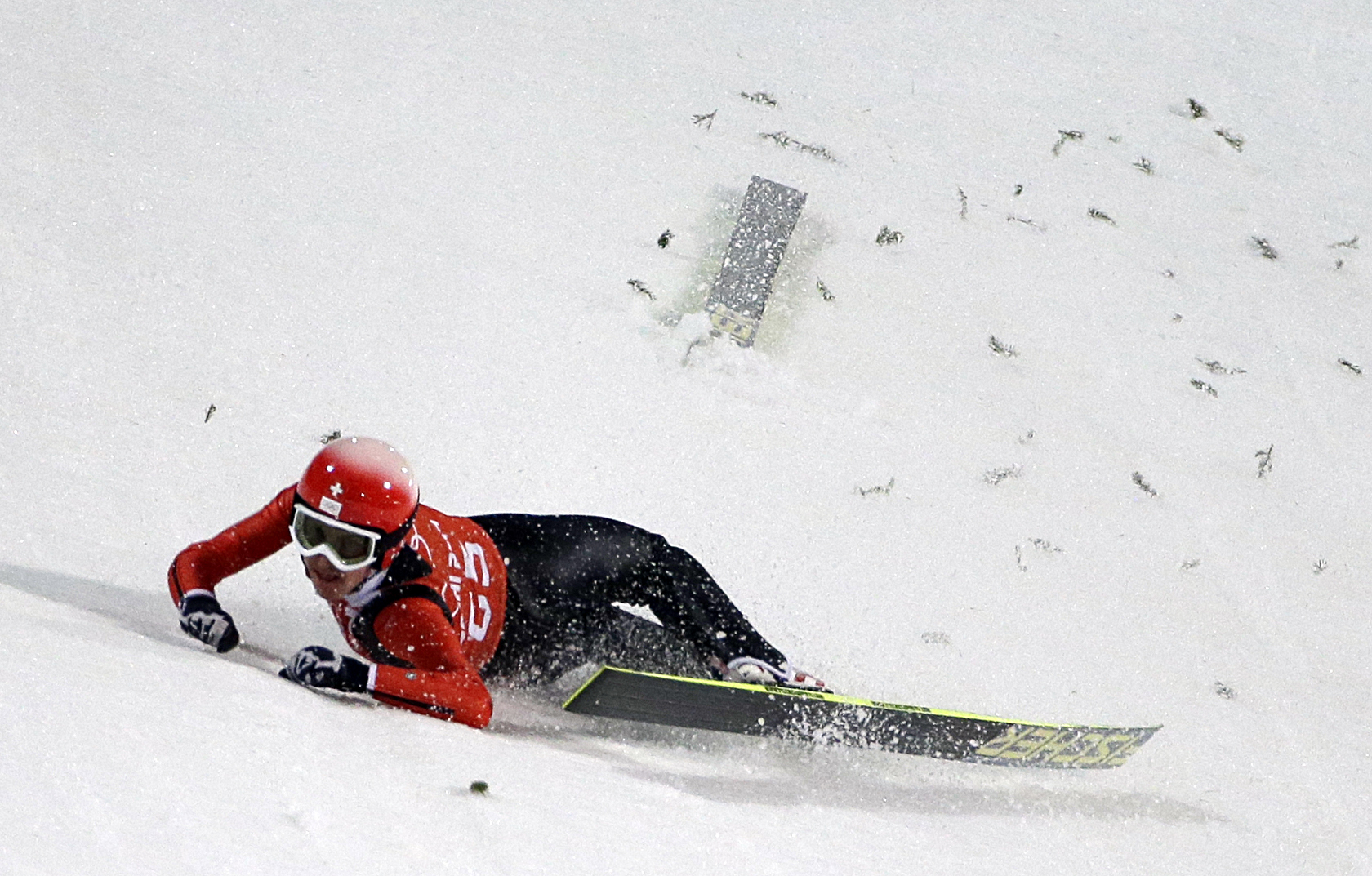 Switzerland's Simon Ammann crashes during a training session for the men's large hill ski jumping at the 2014 Winter Olympics, Thursday, Feb. 13, 2014, in Krasnaya Polyana, Russia. (AP Photo/Gregorio Borgia)