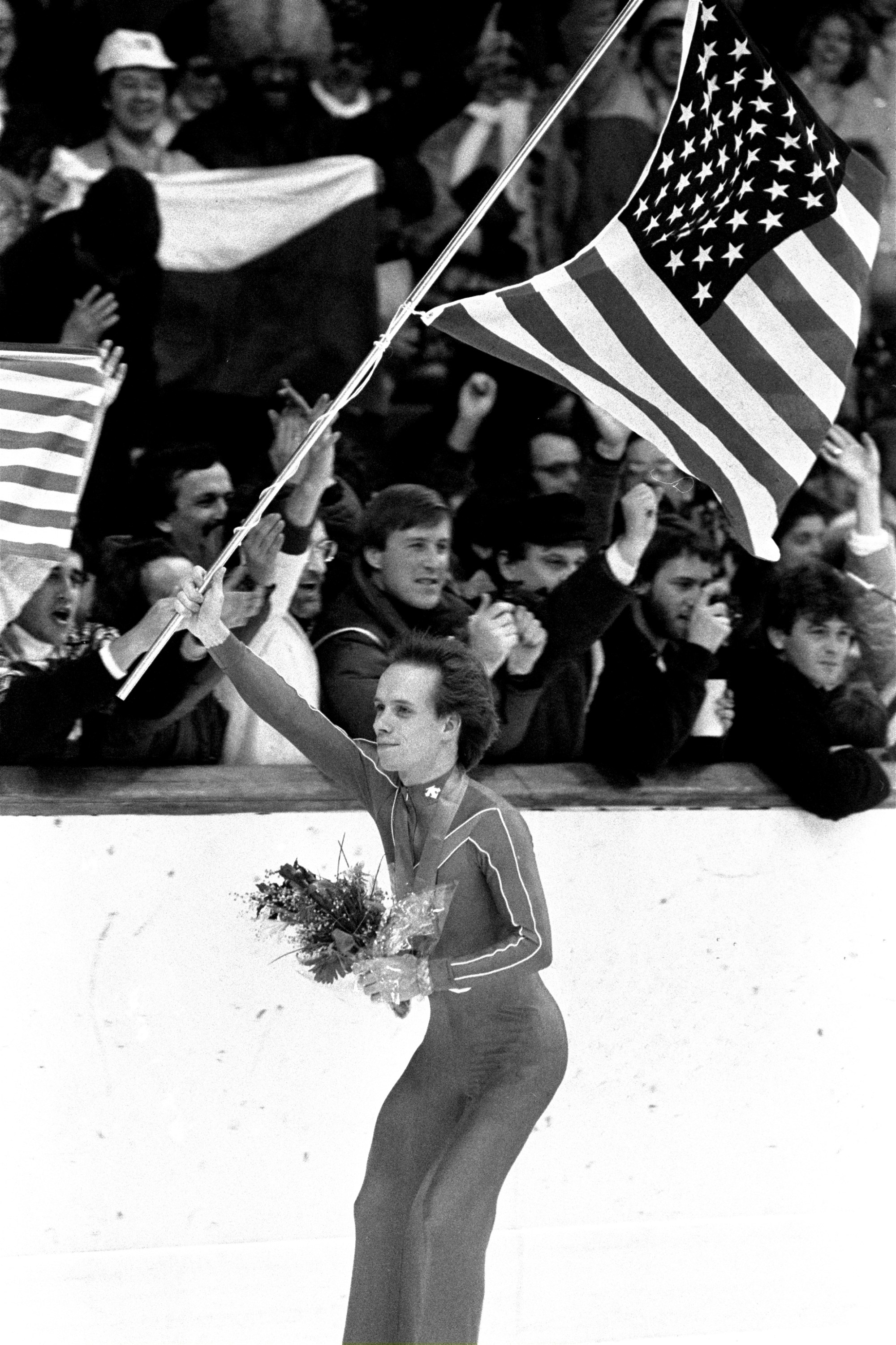"""FILE - In this Feb. 16, 1984 file photo, figure skater Scott Hamilton of the United States carries an American flag past a cheering crowd after he was awarded a gold medal in figure skating at the 1984 Winter Games at Zetra's ice rink in Sarajevo. In the thirty years since his victory, Hamilton has pretty much reinvented professional figure skating by creating """"Stars On Ice"""" and has been the voice of the sport for decades. (AP Photo/File)"""