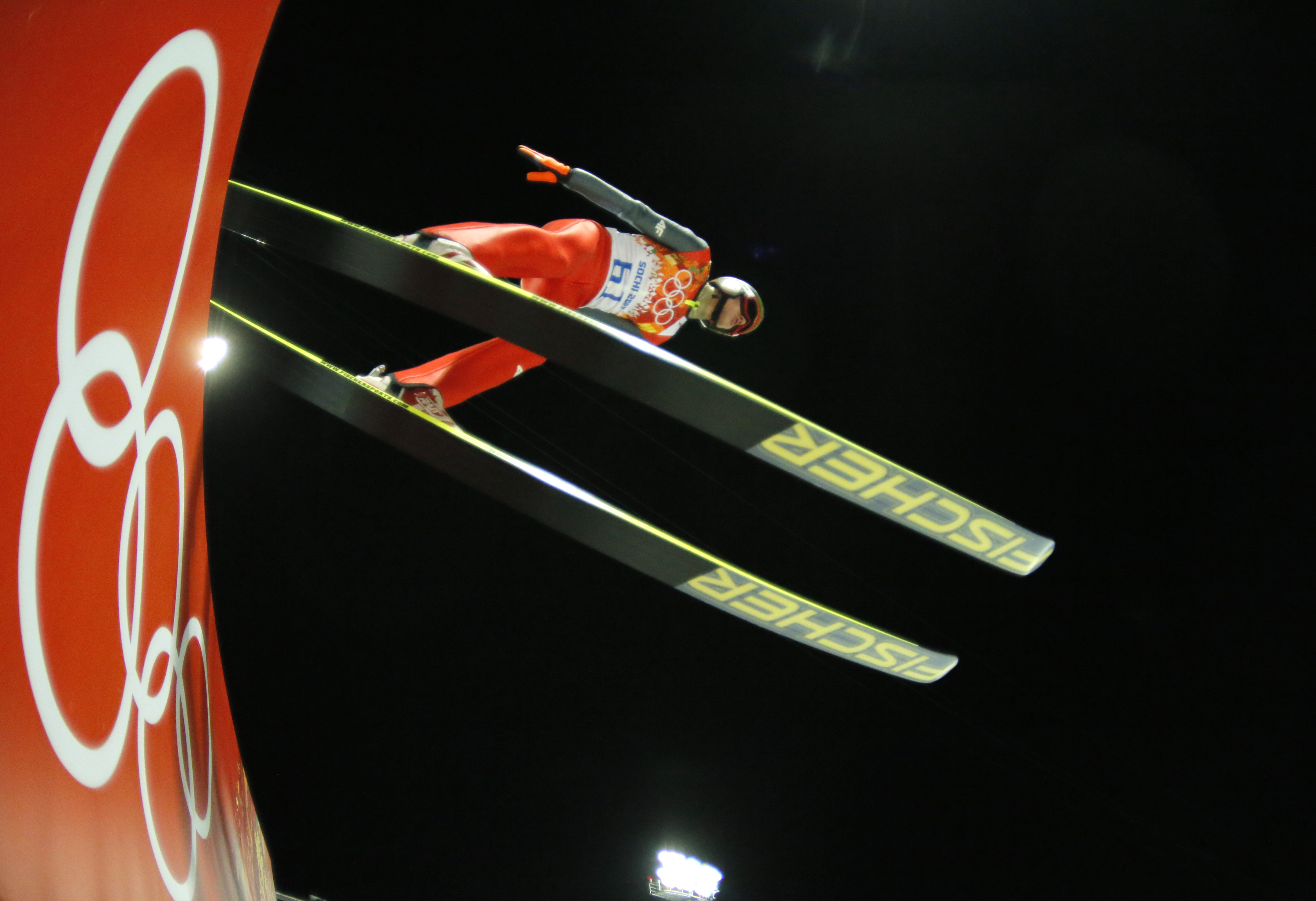 In this photo taken with a fisheye lens Poland's Kamil Stoch makes his trial jump during the ski jumping large hill qualification at the 2014 Winter Olympics, Friday, Feb. 14, 2014, in Krasnaya Polyana, Russia. (AP Photo/Dmitry Lovetsky)