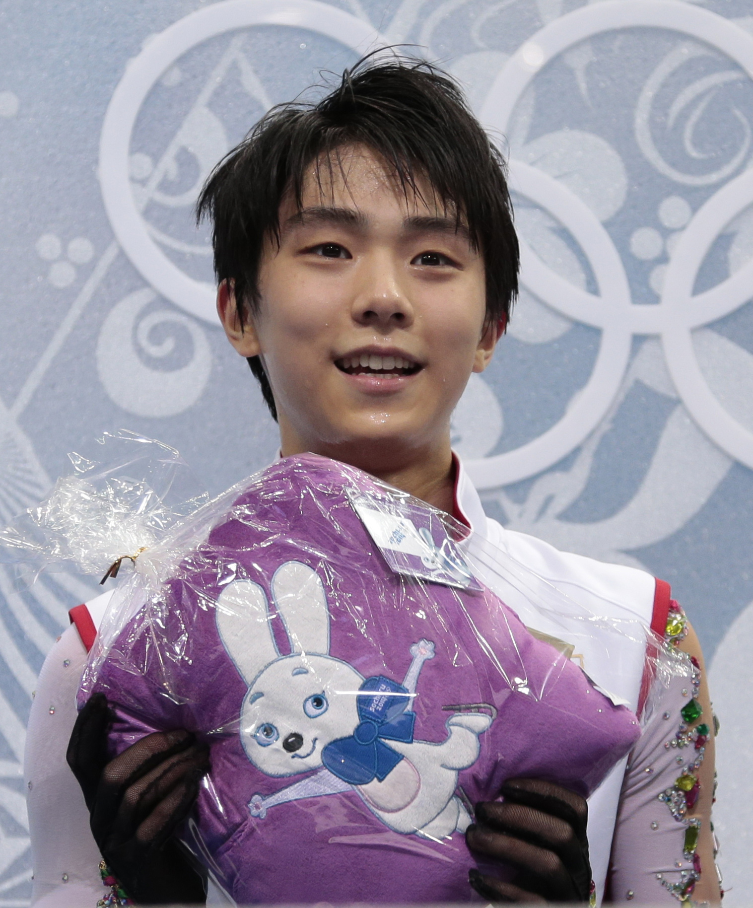 Yuzuru Hanyu of Japan holds an item given to him by a spectator as he sits in the results area after the men's free skate figure skating final at the Iceberg Skating Palace at the 2014 Winter Olympics, Friday, Feb. 14, 2014, in Sochi, Russia. (AP Photo/Ivan Sekretarev)