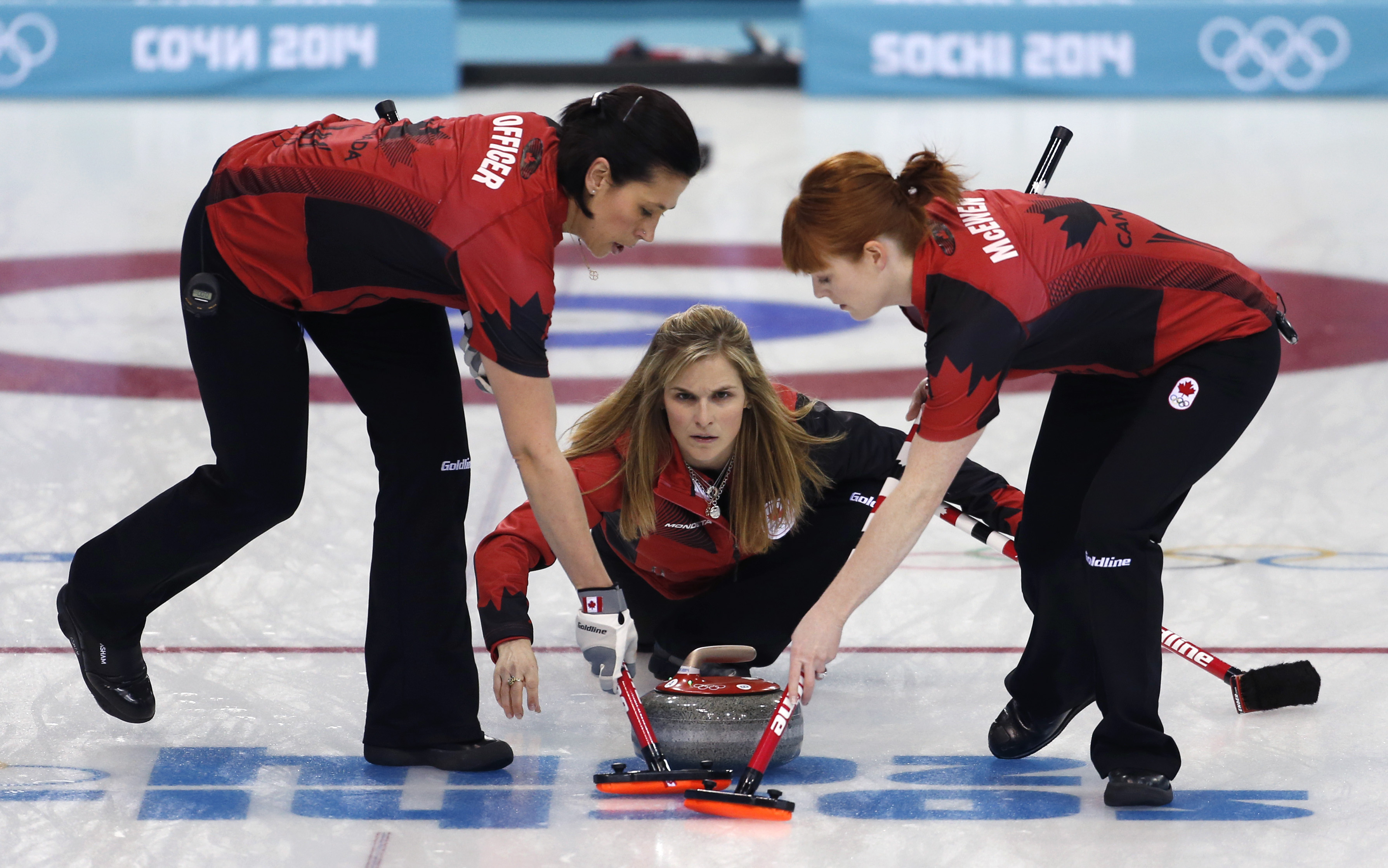 Canada's skip Jennifer Jones, center, delivers the rock to her sweepers Jill Officer, left, and Dawn McEwen during women's curling competition against Japan at the 2014 Winter Olympics, Saturday, Feb. 15, 2014, in Sochi, Russia. (AP Photo/Robert F. Bukaty)