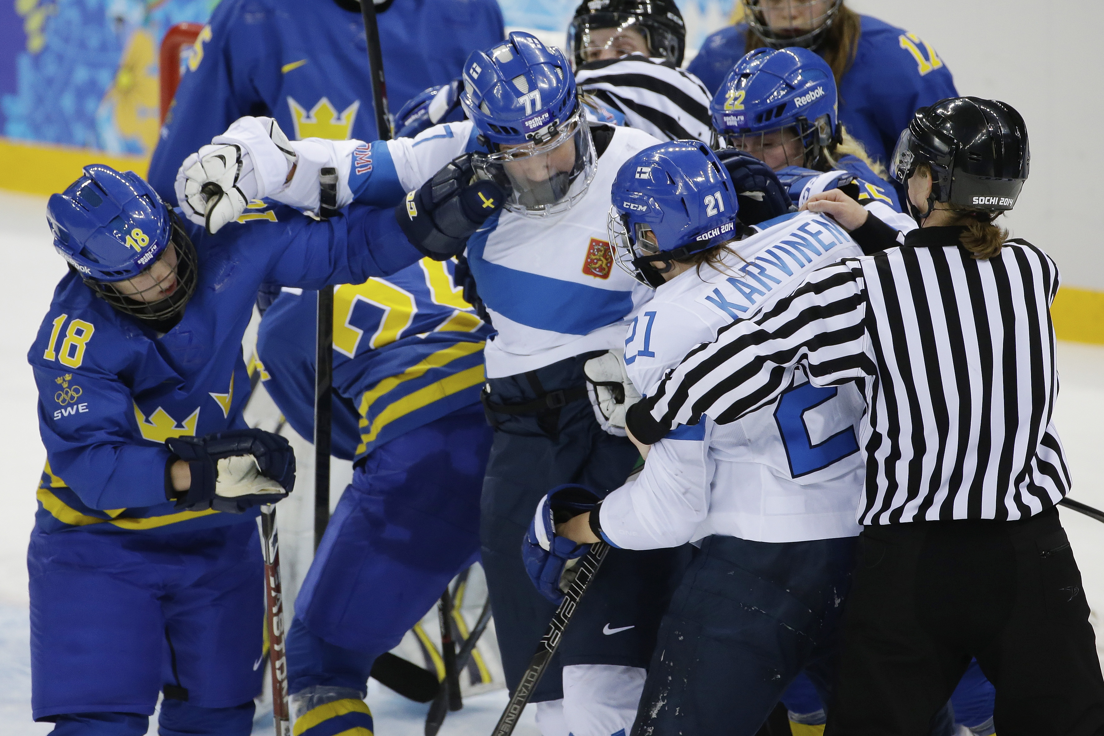 Members of Team Sweden and Team Finland mix it up during the 2014 Winter Olympics women's quarterfinal ice hockey game at Shayba Arena, Saturday, Feb. 15, 2014, in Sochi, Russia. (AP Photo/Matt Slocum)