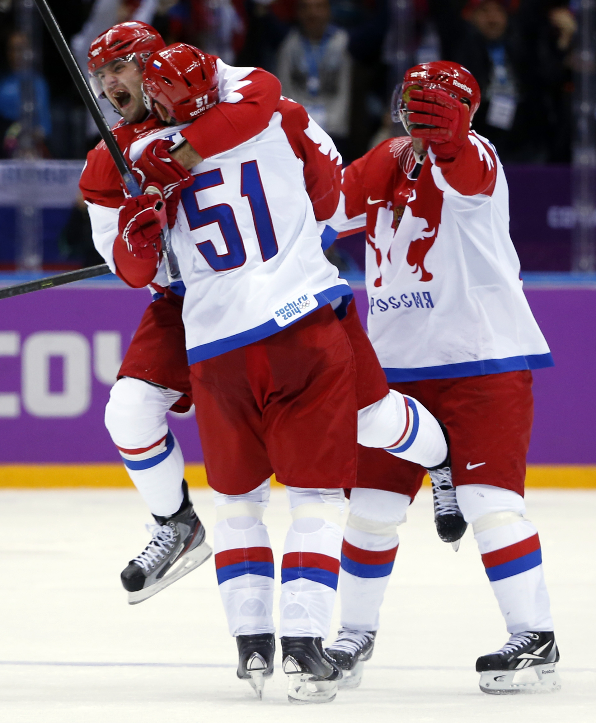 Russia forward Alexander Radulov leaps into the arms of Russia defenseman after a third period goal against the USA during a men's ice hockey game at the 2014 Winter Olympics, Saturday, Feb. 15, 2014, in Sochi, Russia. (AP Photo/Julio Cortez)