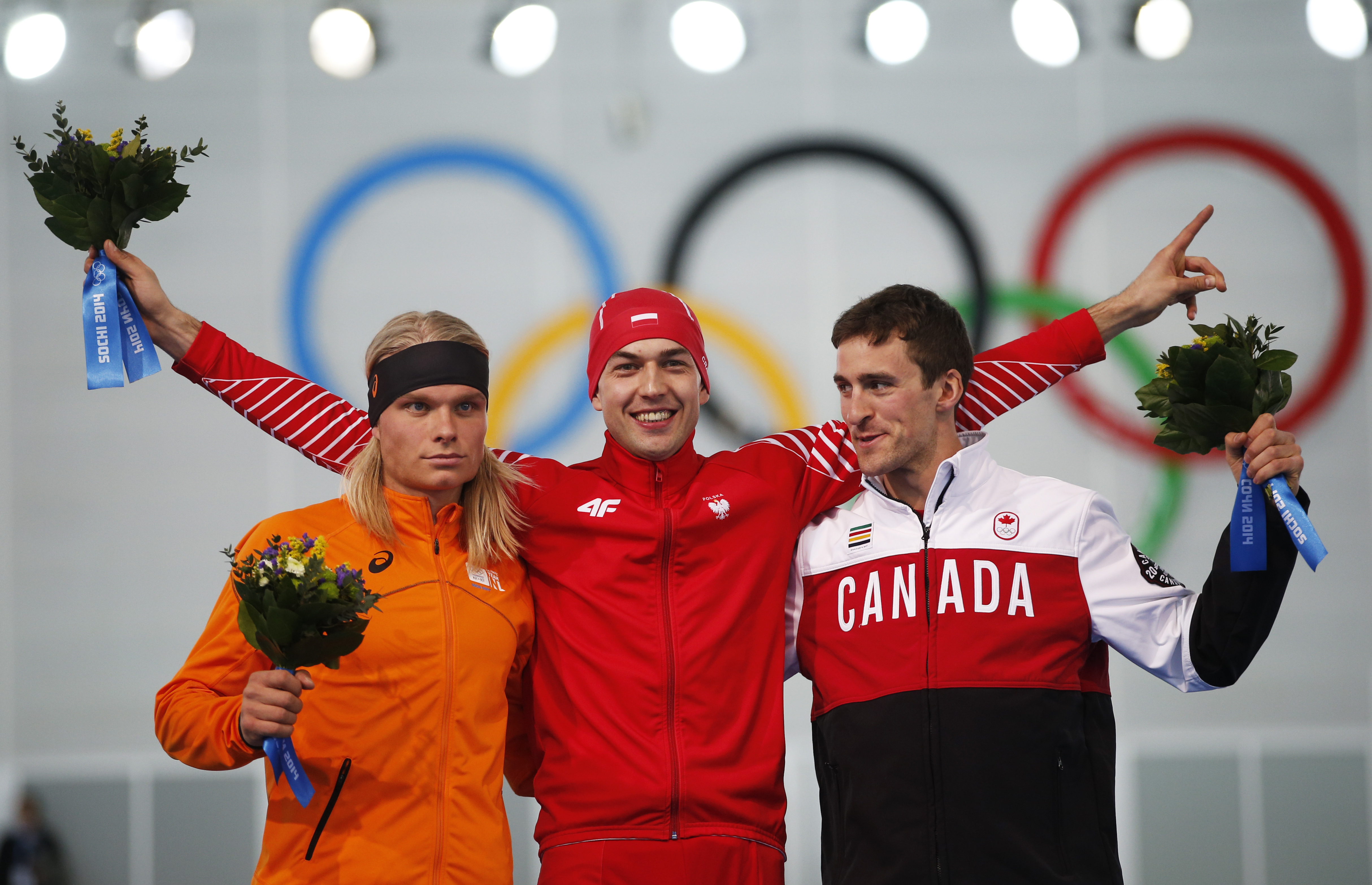 From left to right, silver medallist Koen Verweij of the Netherlands, gold medallist Poland's Zbigniew Brodka and bronze medallist Canada's Denny Morrison stand on the podium during the flower ceremony for the men's 1,500-meter speedskating race at the Adler Arena Skating Center during the 2014 Winter Olympics in Sochi, Russia, Saturday, Feb. 15, 2014. Verweij lost the gold medal by three thousandth of a second. (AP Photo/Pavel Golovkin)