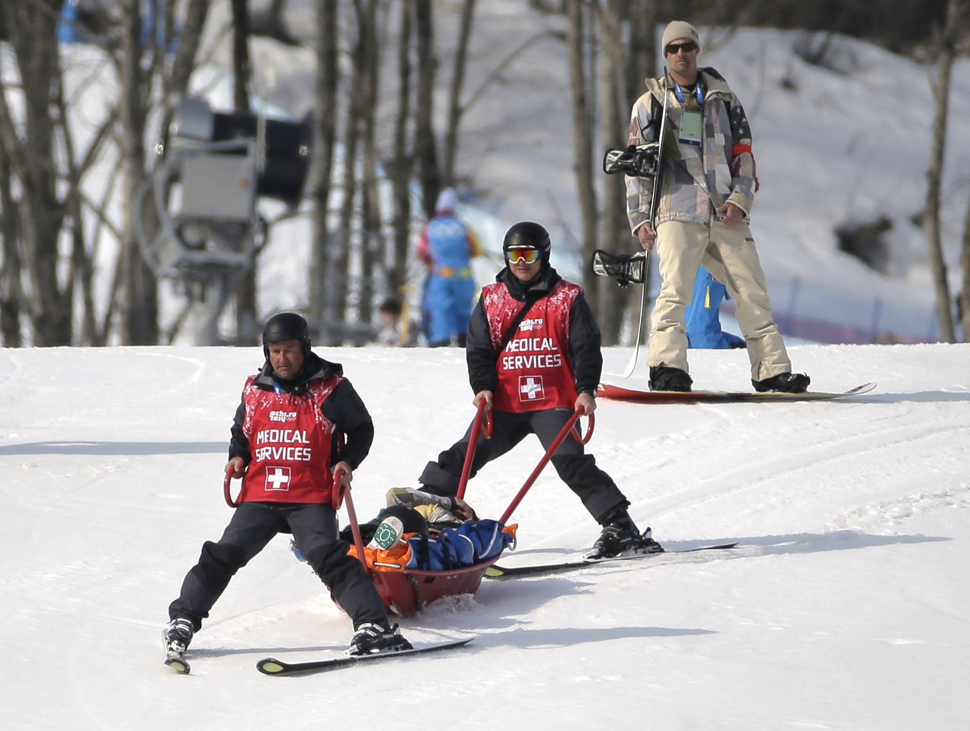 Jacqueline Hernandez of the United States is carried off the course in a stretcher after crashing in a seeding run during women's snowboard cross competition at the Rosa Khutor Extreme Park, at the 2014 Winter Olympics, Sunday, Feb. 16, 2014, in Krasnaya Polyana, Russia. (AP Photo/Andy Wong)