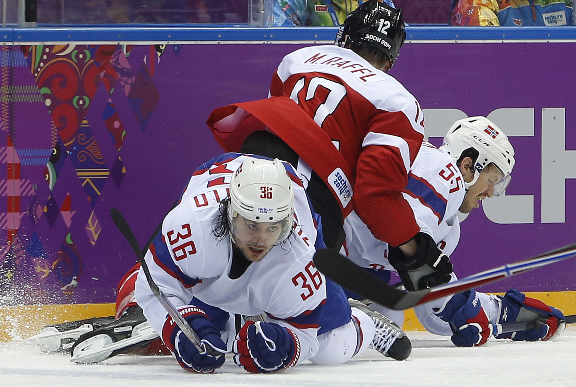 Norway forward Mats Zuccarello gets tangled up with Austria forward Michael Raffl (12) and Norway defenseman Ole-Kristian Tollefsen in the third period of a men's ice hockey game at the 2014 Winter Olympics, Sunday, Feb. 16, 2014, in Sochi, Russia. (AP Photo/Mark Humphrey)