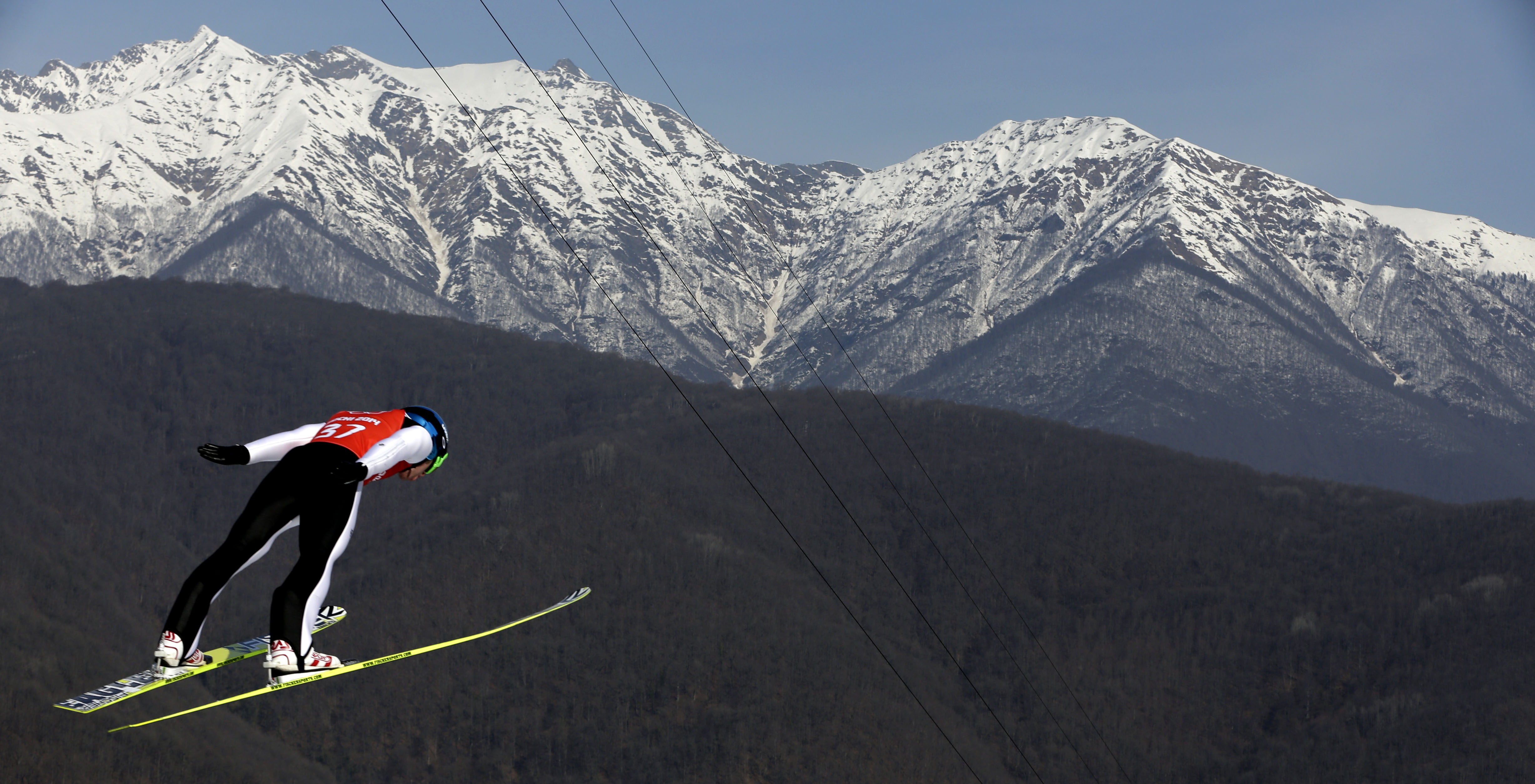 Alessandro Pittin soars through the air during a Nordic Combined training at the 2014 Winter Olympics, Sunday, Feb. 16, 2014, in Krasnaya Polyana, Russia. (AP Photo/Matthias Schrader)