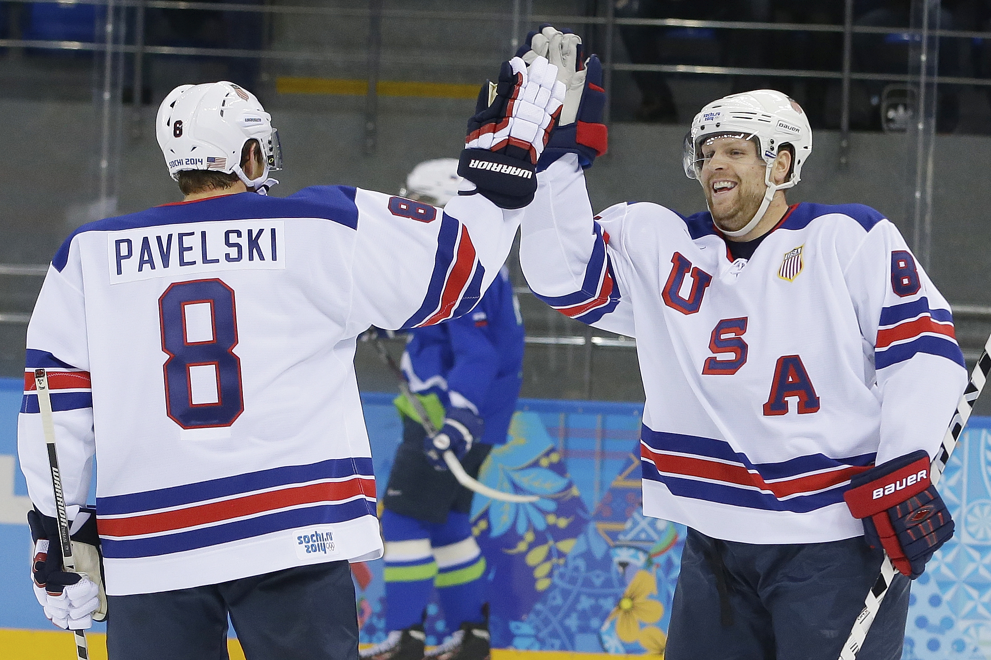 USA forward Phil Kessel, right, celebrates his second goal with teammate Joe Pavelski during the 2014 Winter Olympics men's ice hockey game against Slovenia at Shayba Arena Sunday, Feb. 16, 2014, in Sochi, Russia. (AP Photo/Matt Slocum)