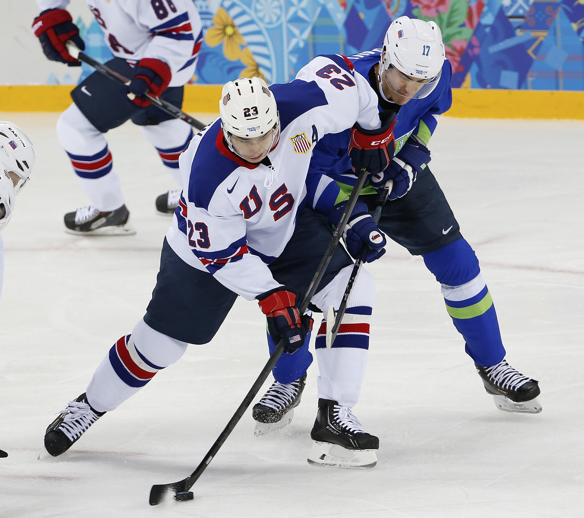 USA forward Dustin Brown takes control of the puck away from Slovenia defenseman Ziga Pavlin during the 2014 Winter Olympics men's ice hockey game at Shayba Arena Sunday, Feb. 16, 2014, in Sochi, Russia. (AP Photo/Petr David Josek)