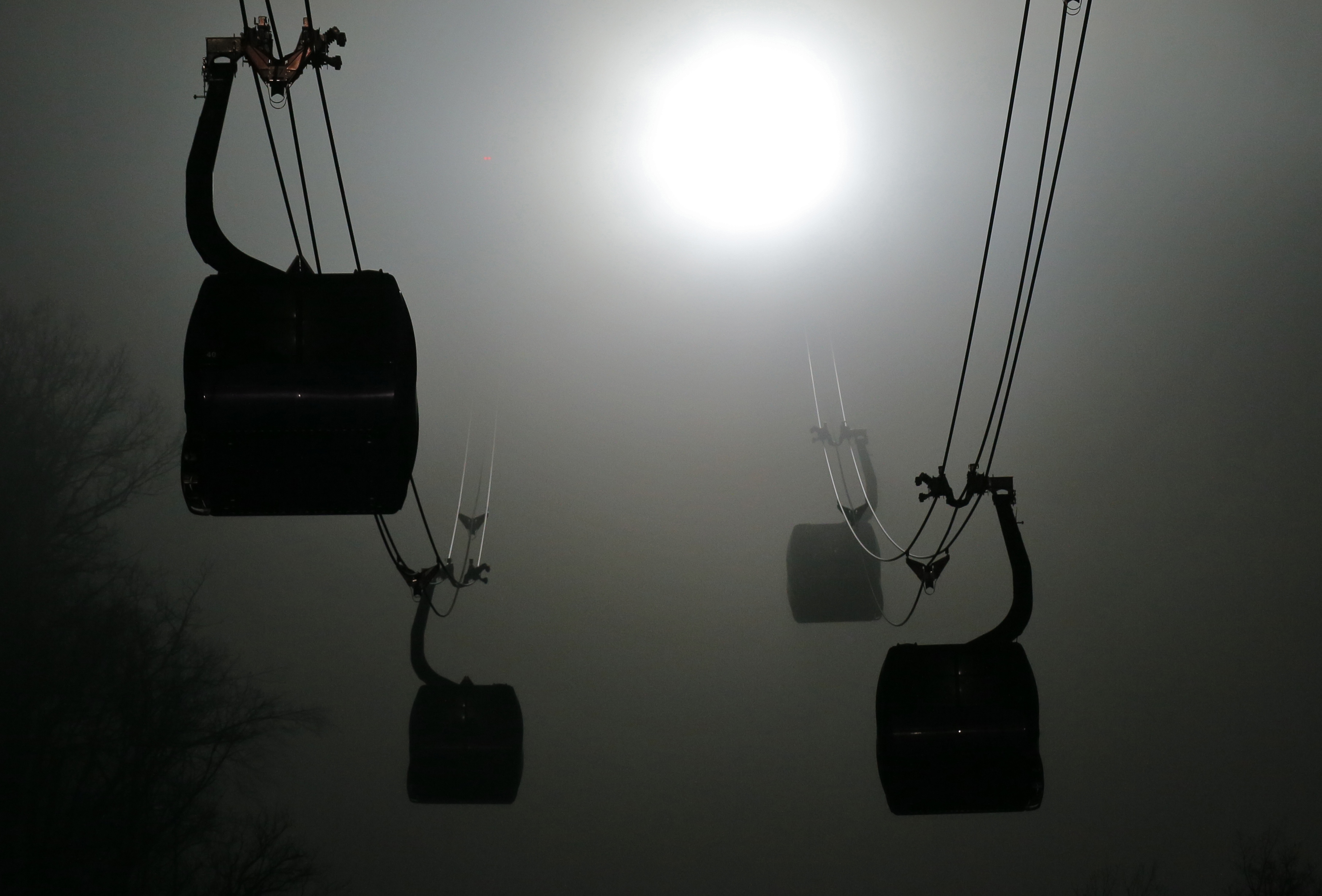 Gondolas are shrouded in fog as they travel to the Laura Cross-country Ski and biathlon venues during the 2014 Winter Olympics in Krasnaya Polyana, Russia, Sunday, Feb. 16, 2014.  (AP Photo/Dmitry Lovetsky)