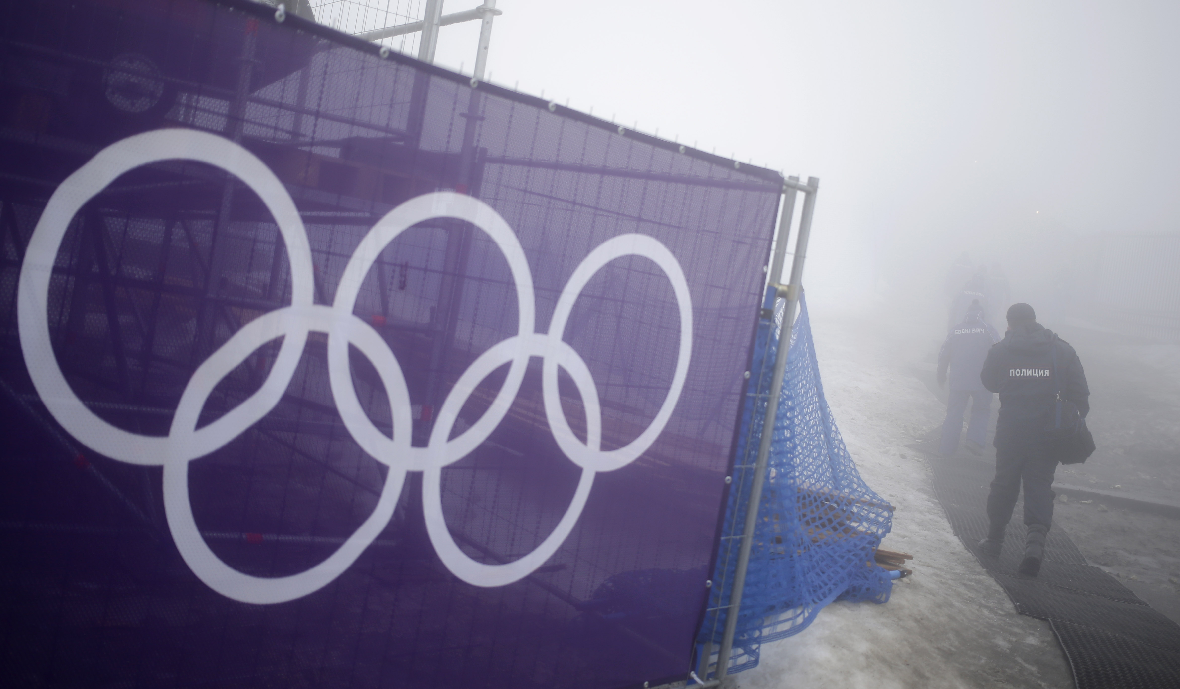 Security guards walk past the Olympic rings prior to a men's snowboard cross competition at the Rosa Khutor Extreme Park, at the 2014 Winter Olympics, Monday, Feb. 17, 2014, in Krasnaya Polyana, Russia. (AP Photo/Andy Wong)